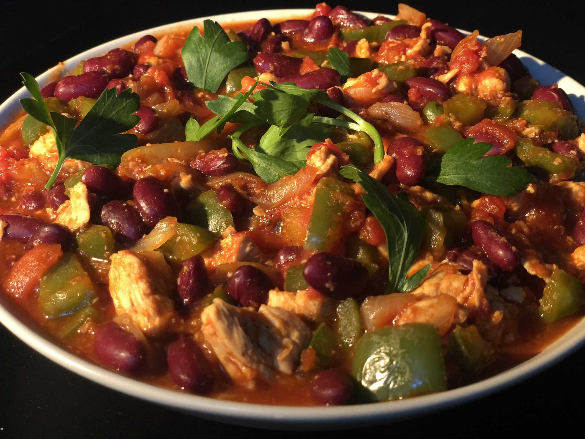 Dans un plat creux, se trouve le poulet coupé en généreux morceaux, les haricots rouges et le poivron baignant dans le chili et la sauce tomate.
