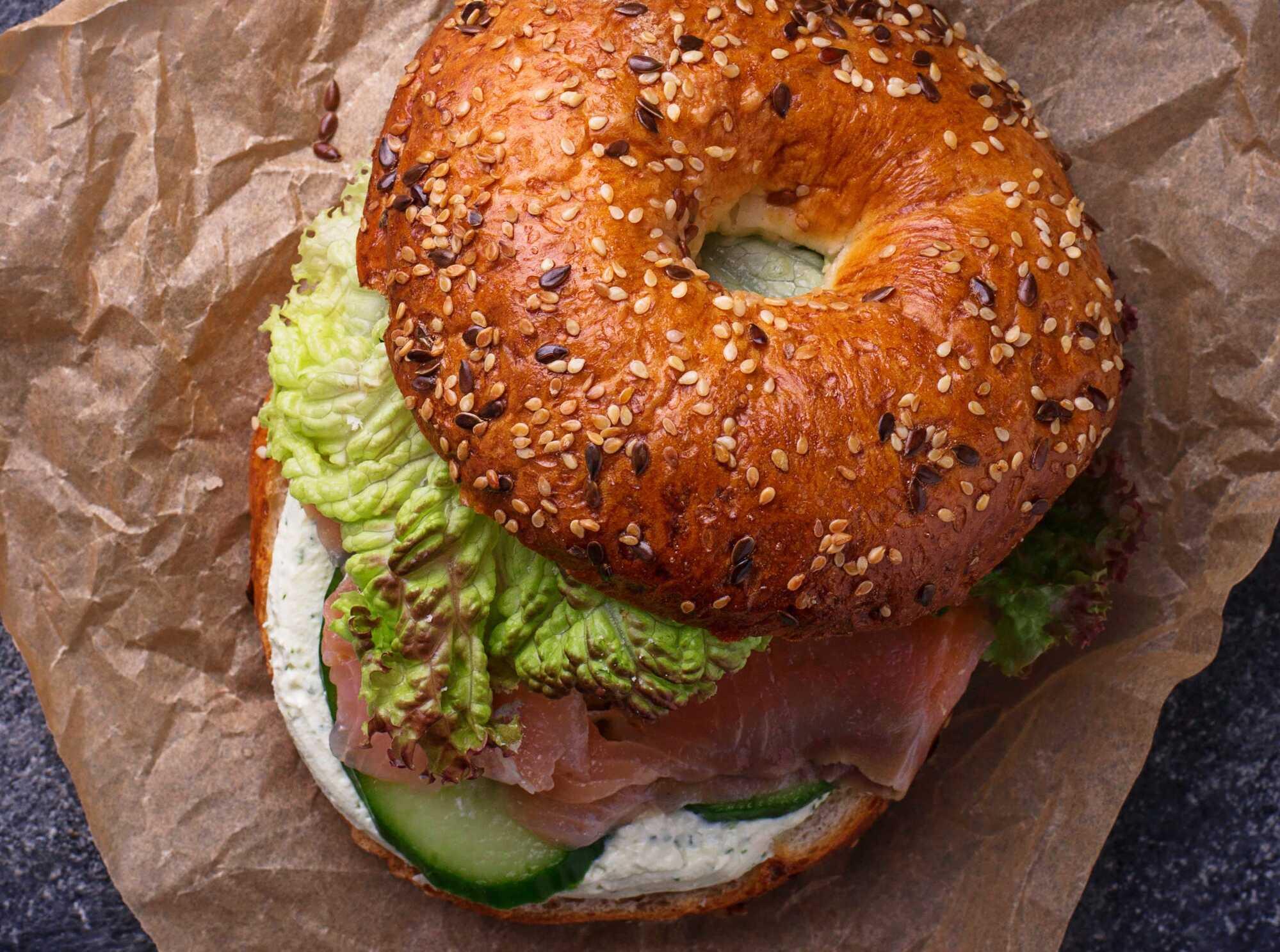 Ce bagel se présente sous la forme d'un burger, avec ses différents aliments, à commercer par les concombres, la tranche de saumon et la salade