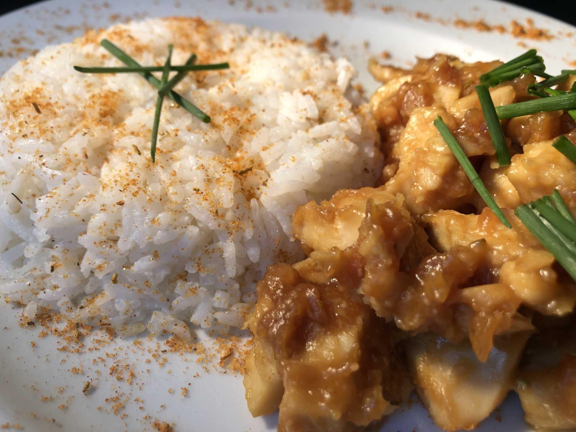 Dans un large plat de couleur blanc, on retrouve d'un côté le riz d'accompagnement et de l'autre le soja. Le tout est parsemé de ciboulette émincée.