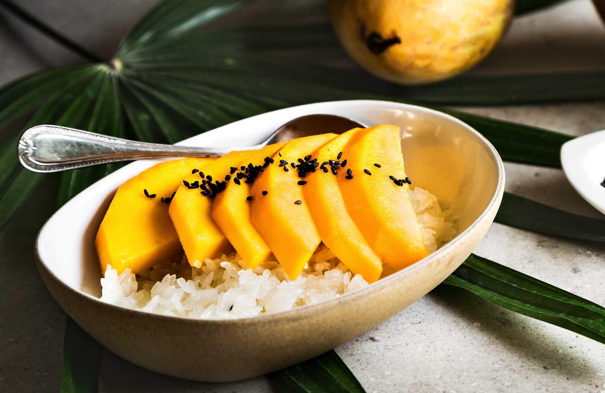 La recette est présentée dans un plat creux et ovale de couleur blanc. Les perles de konjak sont recouvertes par de belles tranches de mangue.