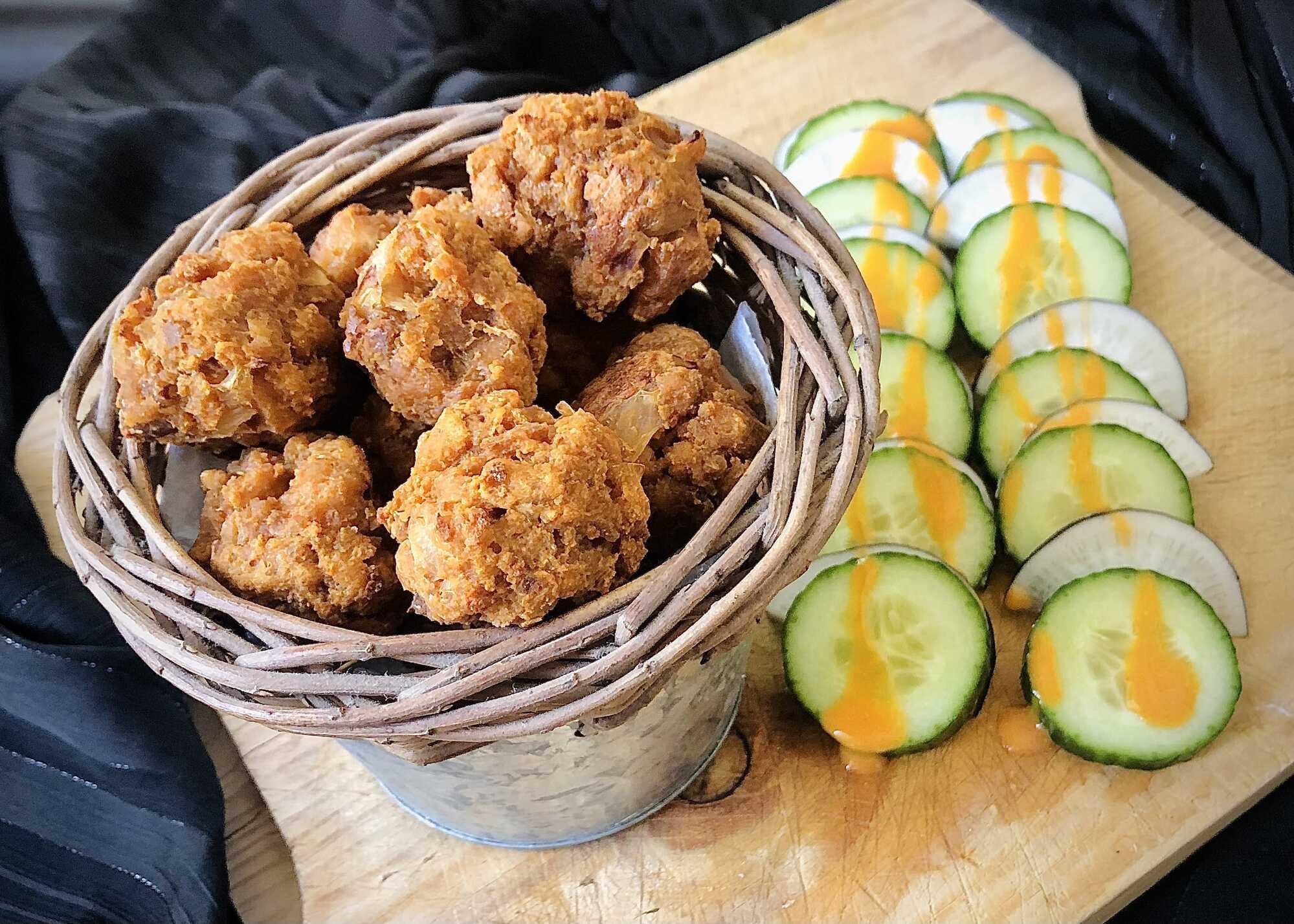 Dans un gros bol, les boulettes de tofu sont dorées par la cuisson. A coté de fines tranches de concombres sont disposées.