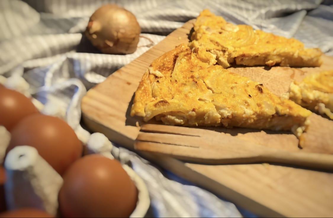 A côté de quelques oeufs, sur une planche en bois et à coté d'une fourchette en bois également, on trouve des morceaux de quiche au potiron et poulet.