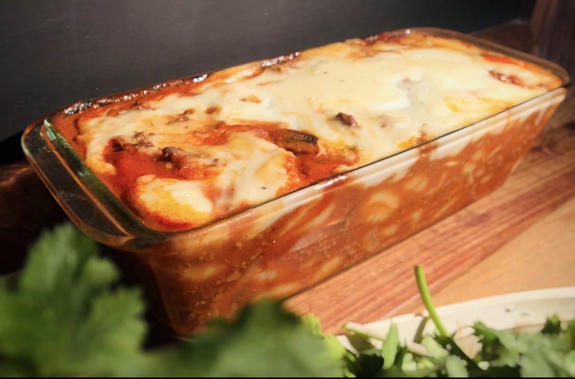 Dans un plat à gratin transparent, la viande et les gnocchis ont pris la coloration des tomates. Au dessus le fromage râpé est joliment gratiné.