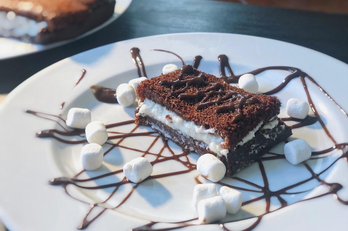 Sur une assiette de blanche, se trouve une jolie tranche de ce dessert avec entre deux couches de chocolat la préparation à base d'amandes