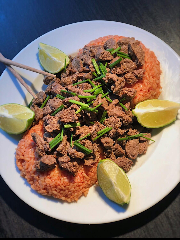 Le riz coloré par la sauce tomate est recouvert par le boeuf. Un citron vert coupé en quatre est disposé autour du plat.