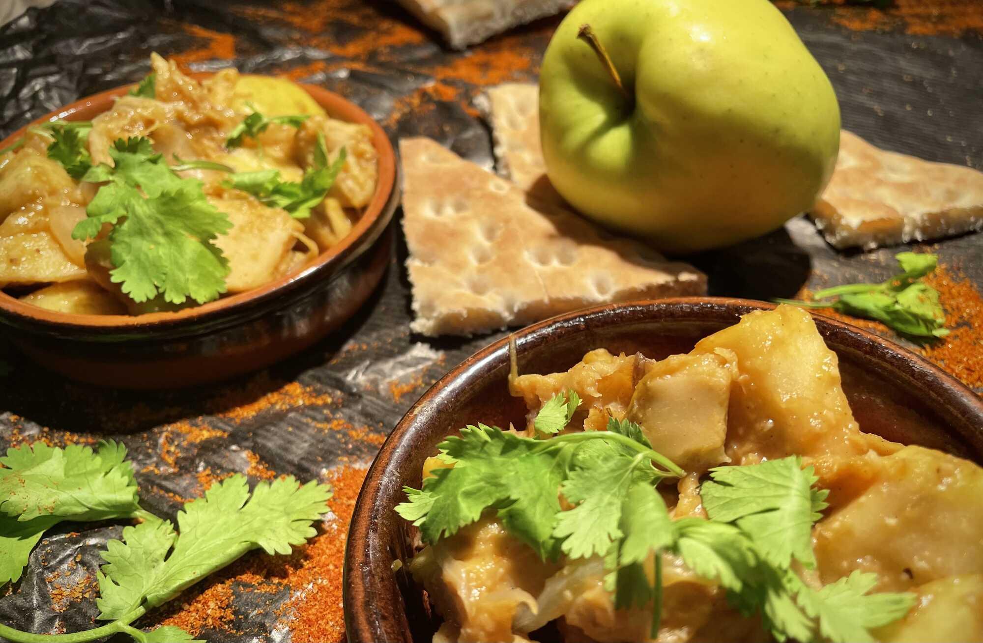 Le soja à l'indienne est présenté dans deux plats ronds en terre cuite. Sur la table on peut voir une belle pomme verte.