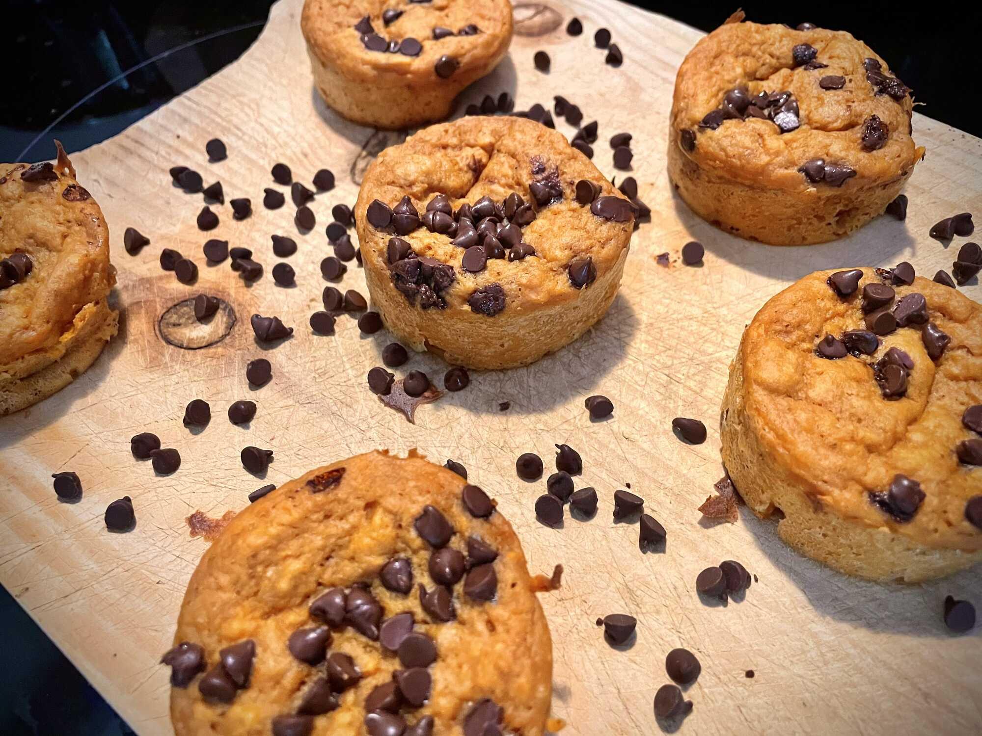 Sur un plateau de bois clair sont disposés six beaux muffins bien dorés saupoudrés de pépites de chocolat.