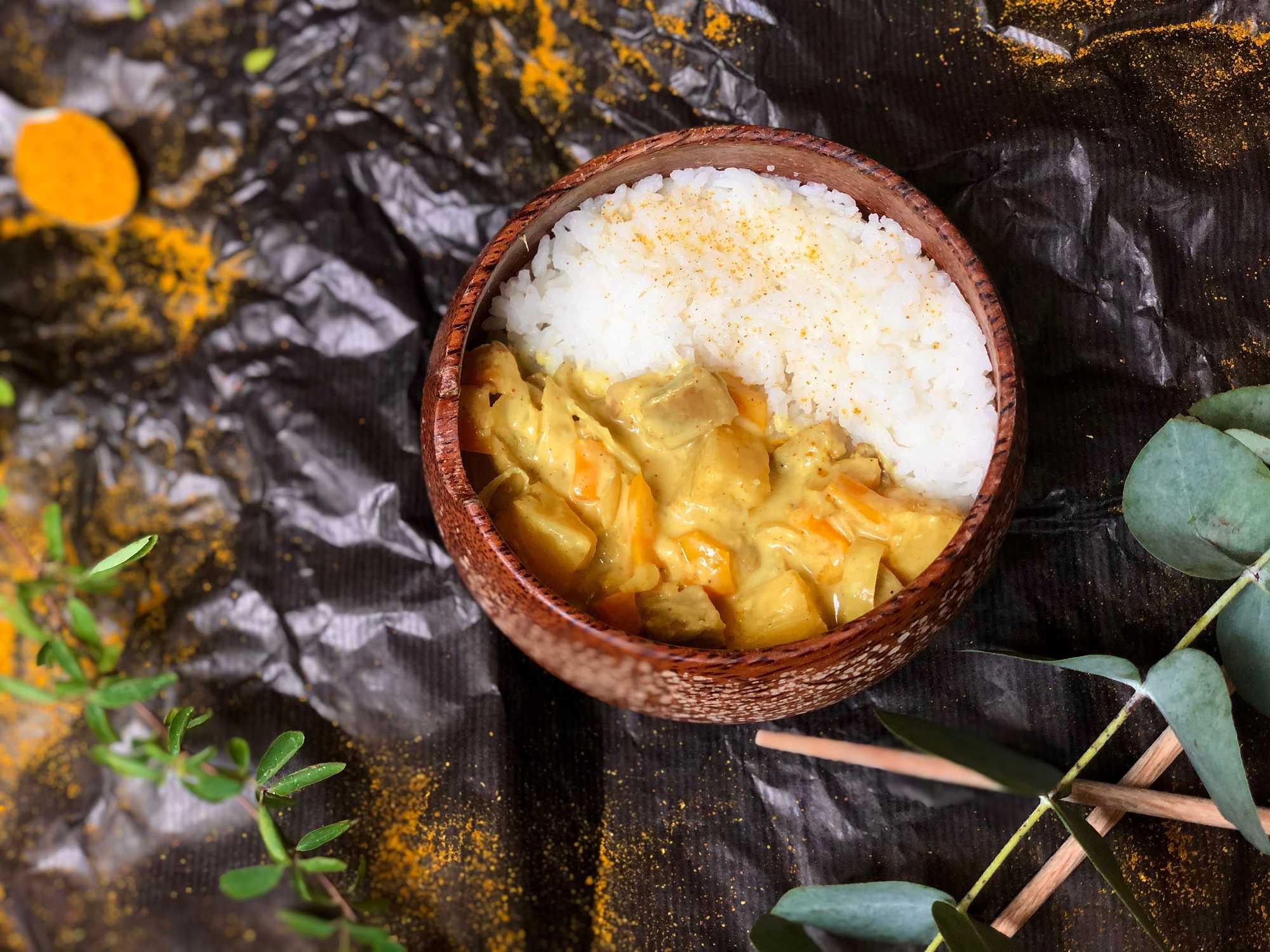 Dans un grand bol en faïance, on retrouve d'un côté l'ananas et le seitan coupé en petits morceaux, et de l'autre côté du riz.