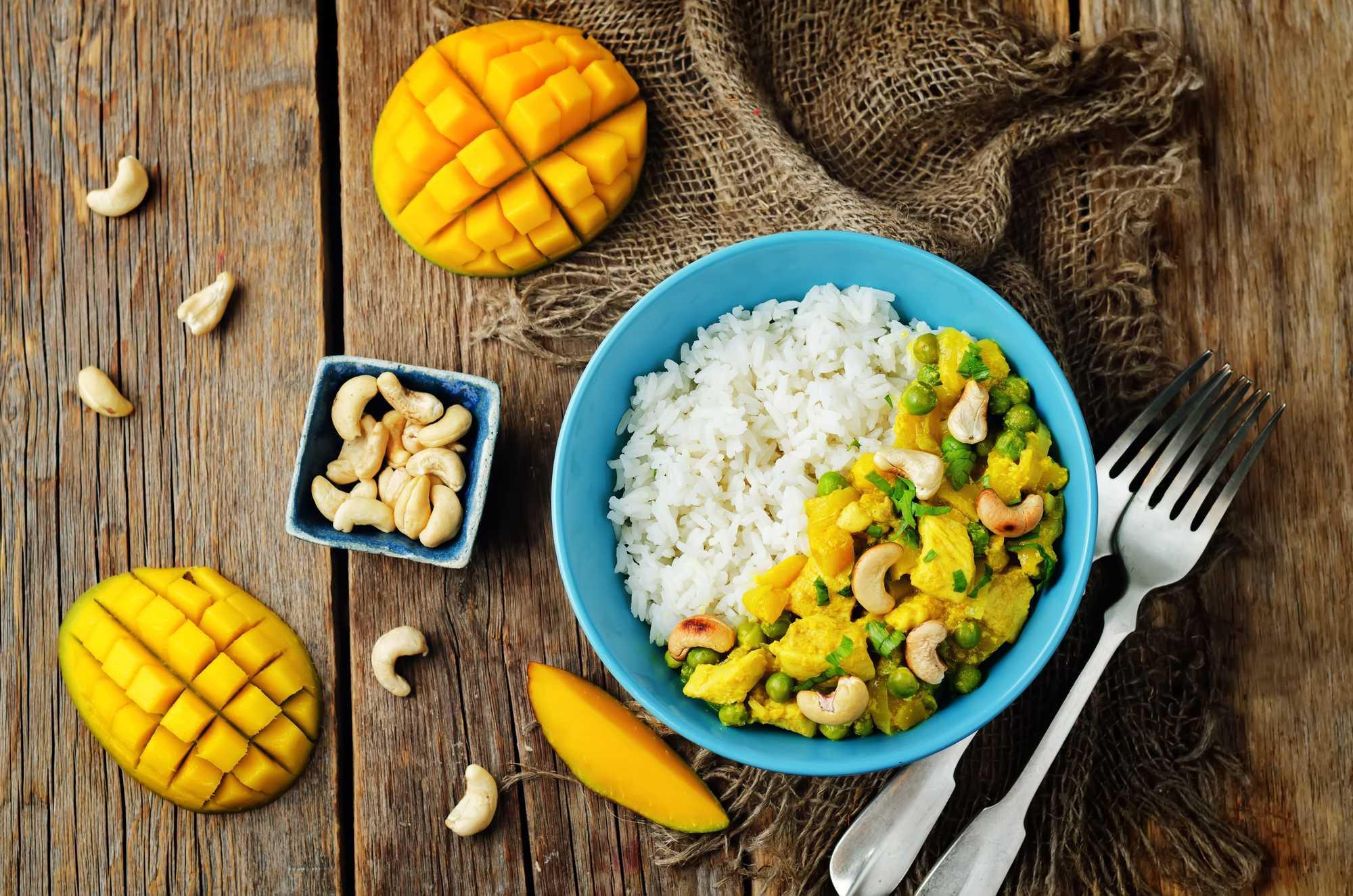 Dans un grand bol de couleur bleu, se trouve le poulet accompagné avec du riz. Sur la table une mangue sans sa peau est prédécoupée en petits dés.
