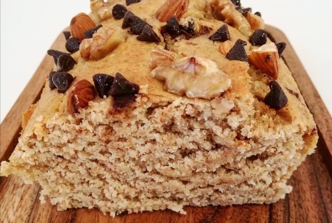 Sur un plateau en bois, on retrouve le Cakepote avec sa belle couleur ambrée. Le topping est composé de pépites de chocolat, d'amandes et de noix.