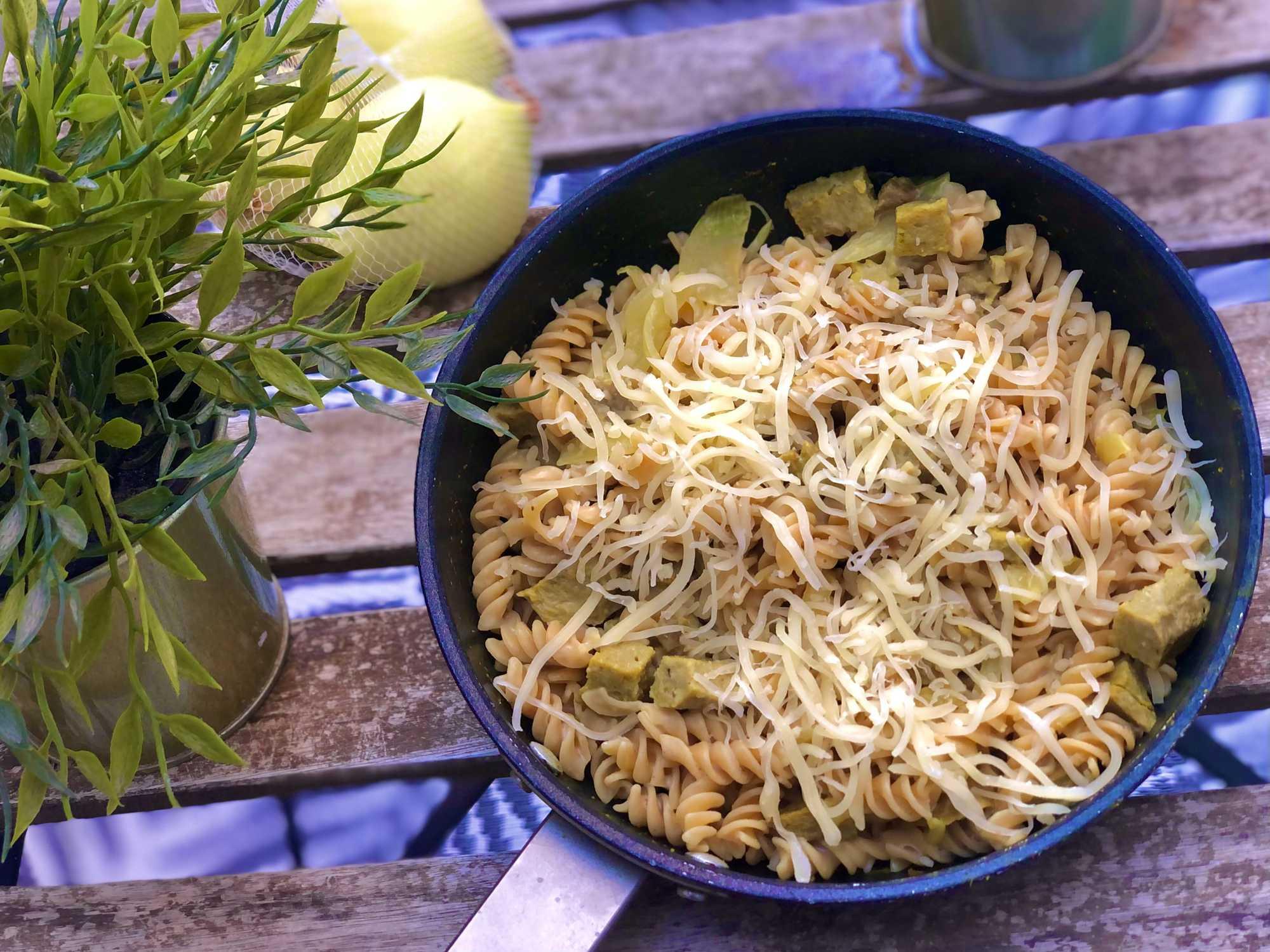 Posé sur une table de jardin, on peut voir une poêle avec les pâtes de lentilles corail qui recouvrent le seitan. Deux citrons sont posés à côté.