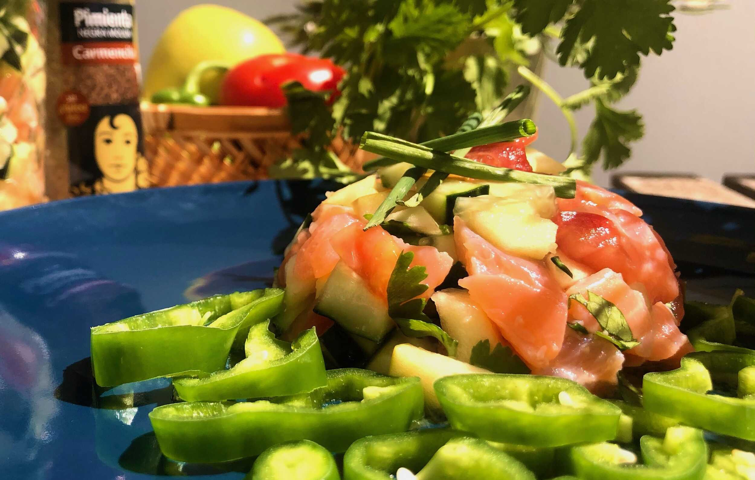Ce tartare de saumon aux saveurs et aux couleurs de l'été est présenté dans un plat de couleur bleu nuit.