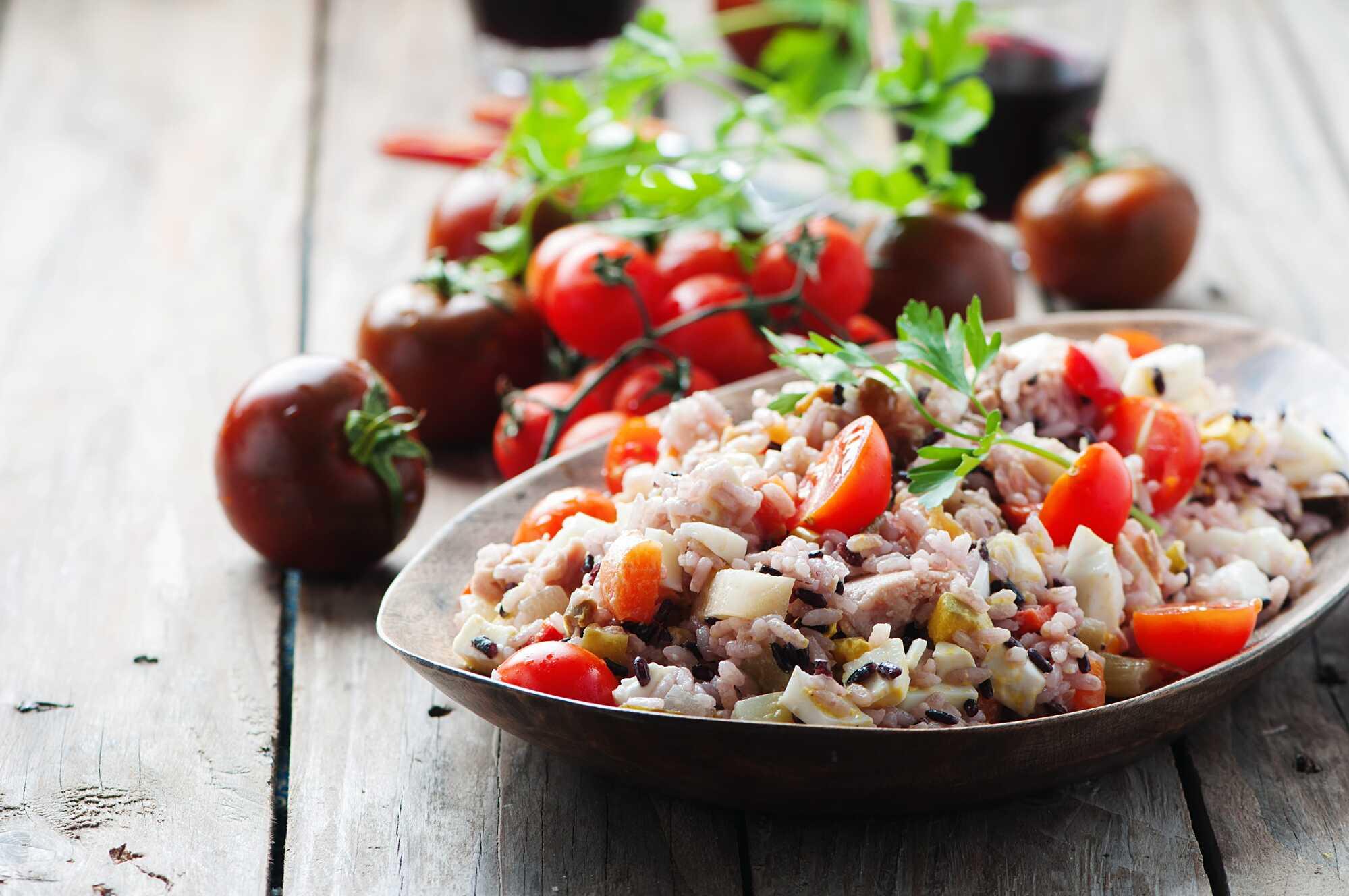 Un plat creux reçoit la salade de riz avec les tomates cerises coupées en deux, le thon et le Comté.
