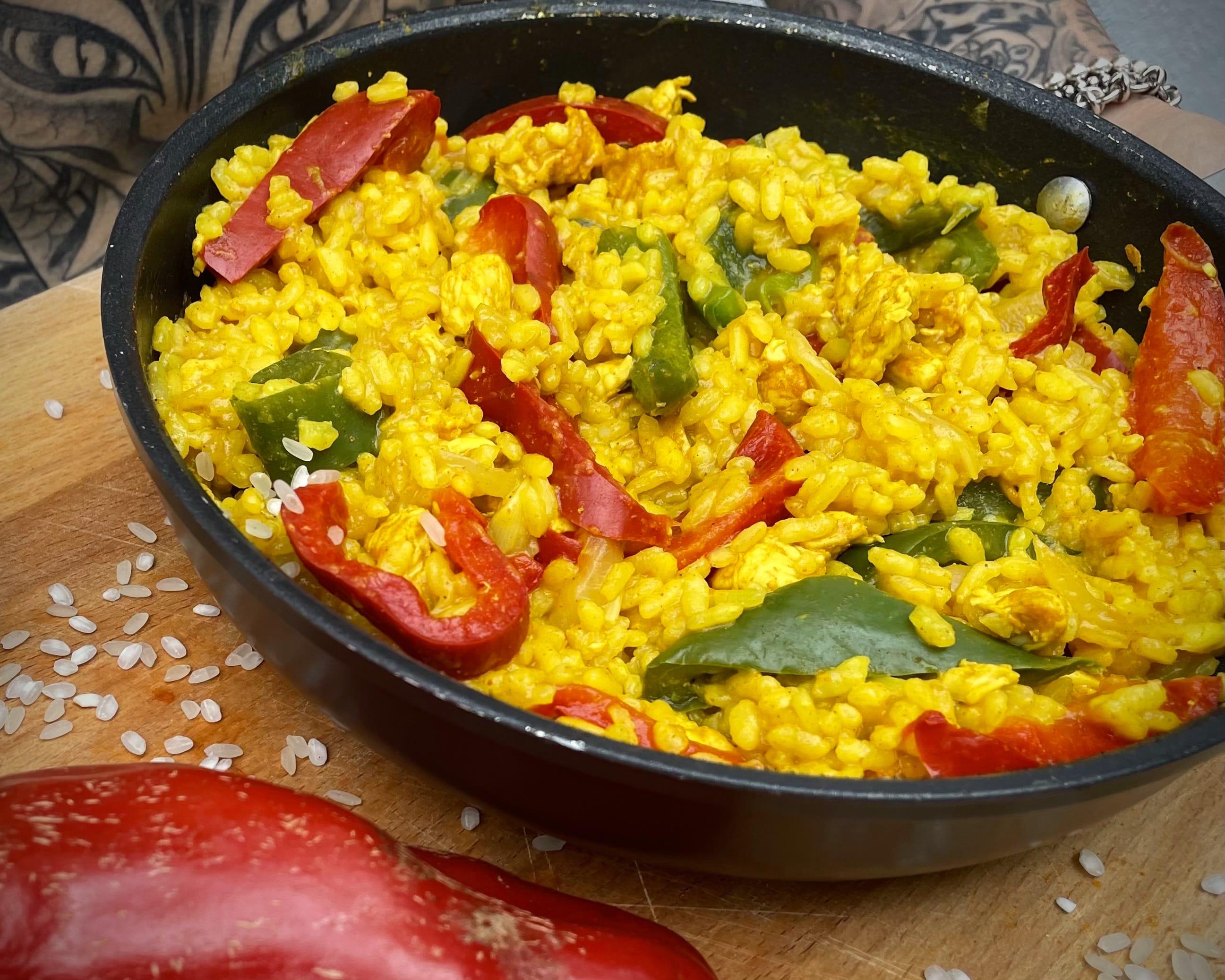 Dans un grand saladier se trouve le riz coloré par le curcuma. Les poivrons verts et rouges apportent une touche de couleur.