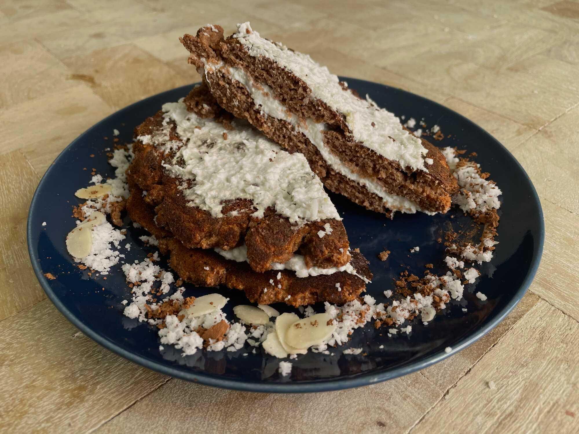 Deux pancakes sont présentés sur une assiette de couleur foncé, ils sont recouverts de chocolat et de noix de coco râpée.