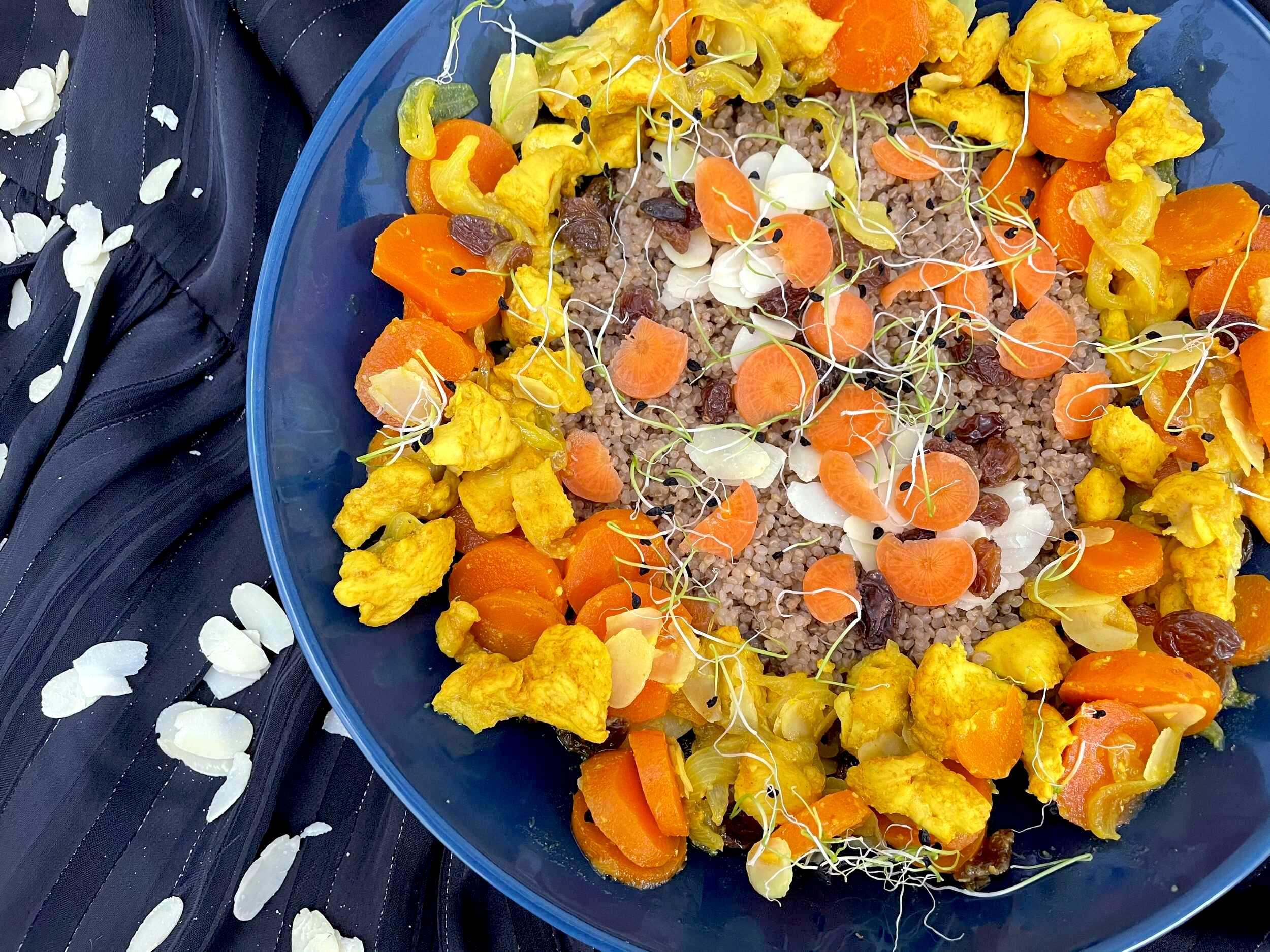 Dans un plat bleue on retrouve le poulet, les carottes, les raisins et les amandes effilées. Très appétissant.