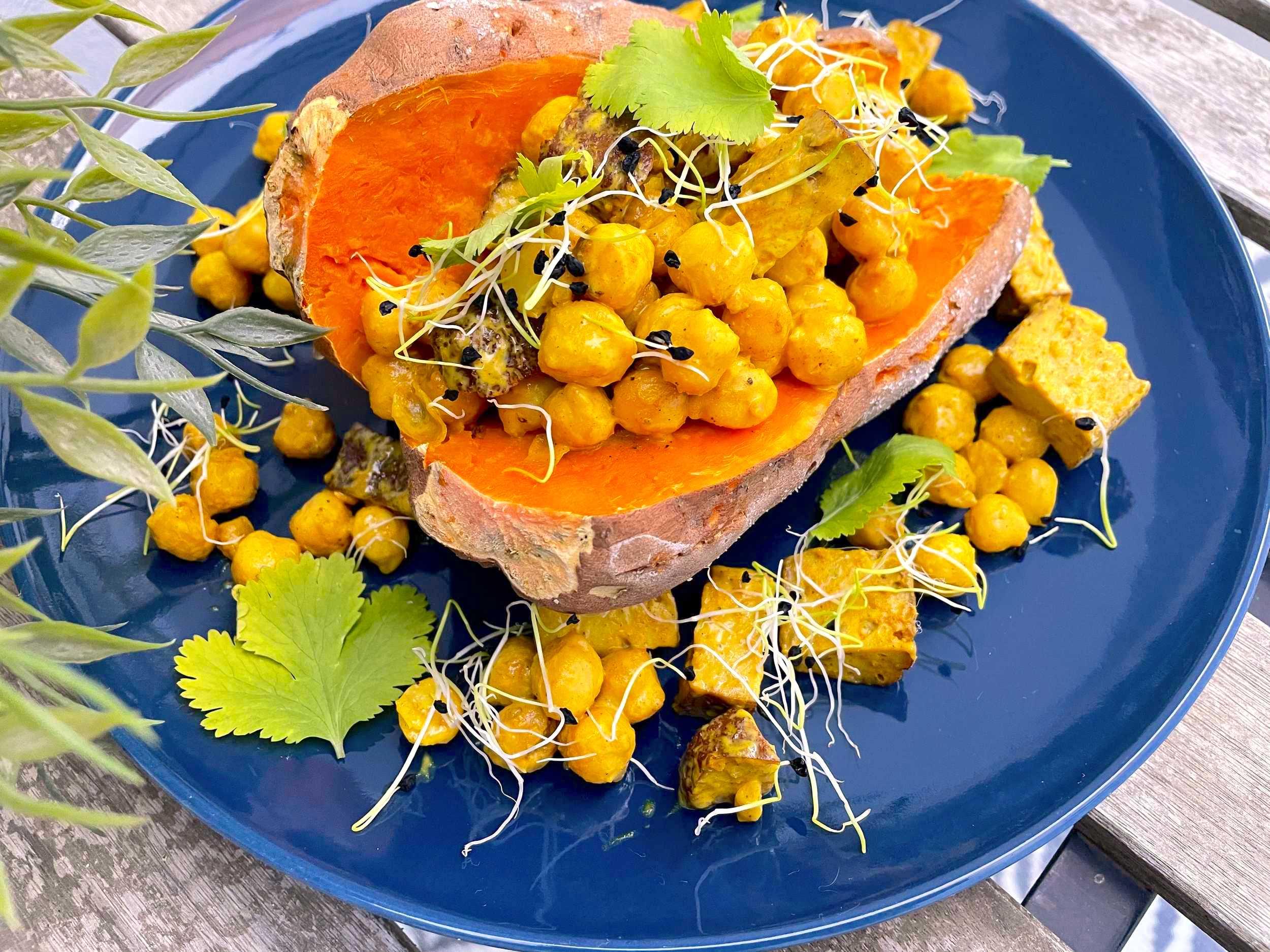 Sur une assiette bleue, la patate douce est fourrée par le mélange pois chiches et seitan. La coriandre fraîche est parsemée sur le dessus.