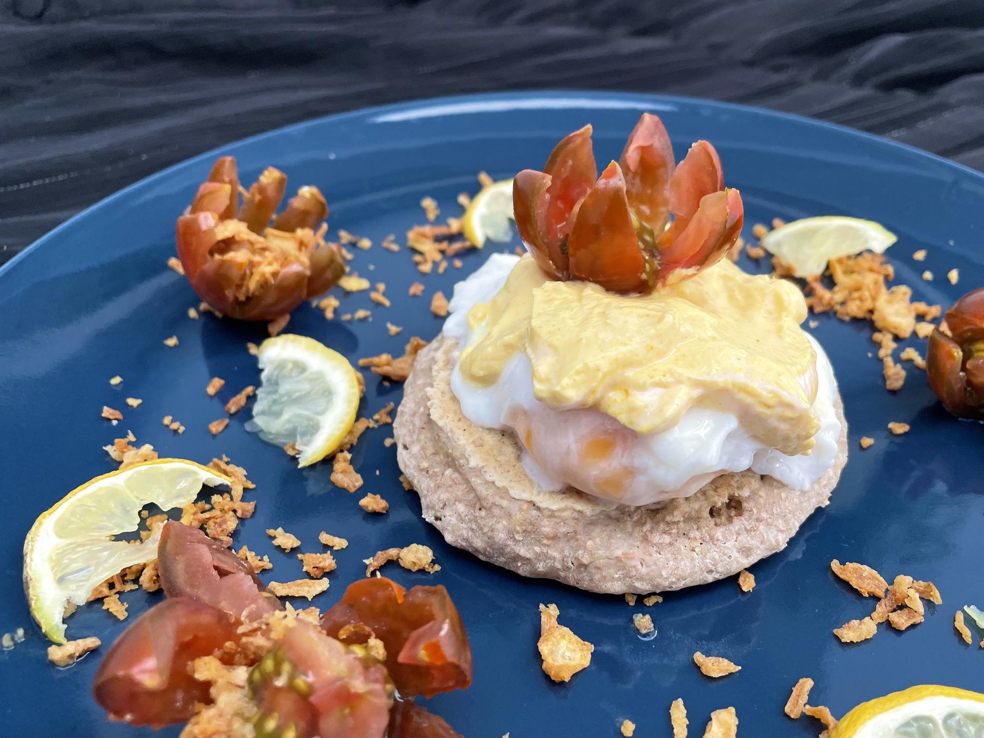 Le crumpet est surmonté par les oeufs et recouvert de la sauce à base de fromage blanc. Le tout est présenté sur une belle assiette bleue.