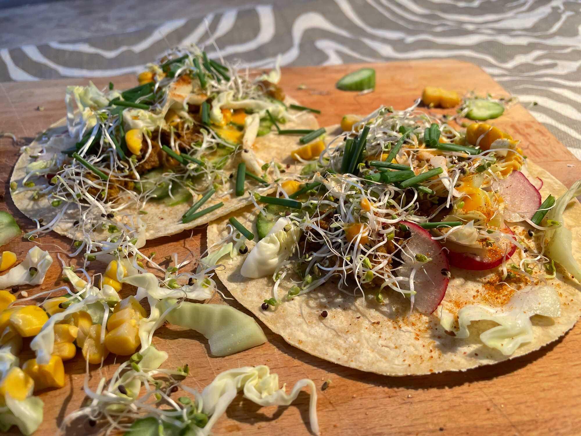 Sur un plat couleur orange, deux beaux tacos non pliés sont garnies des différents ingrédients dont les gros morceaux de concombres et le tofu.