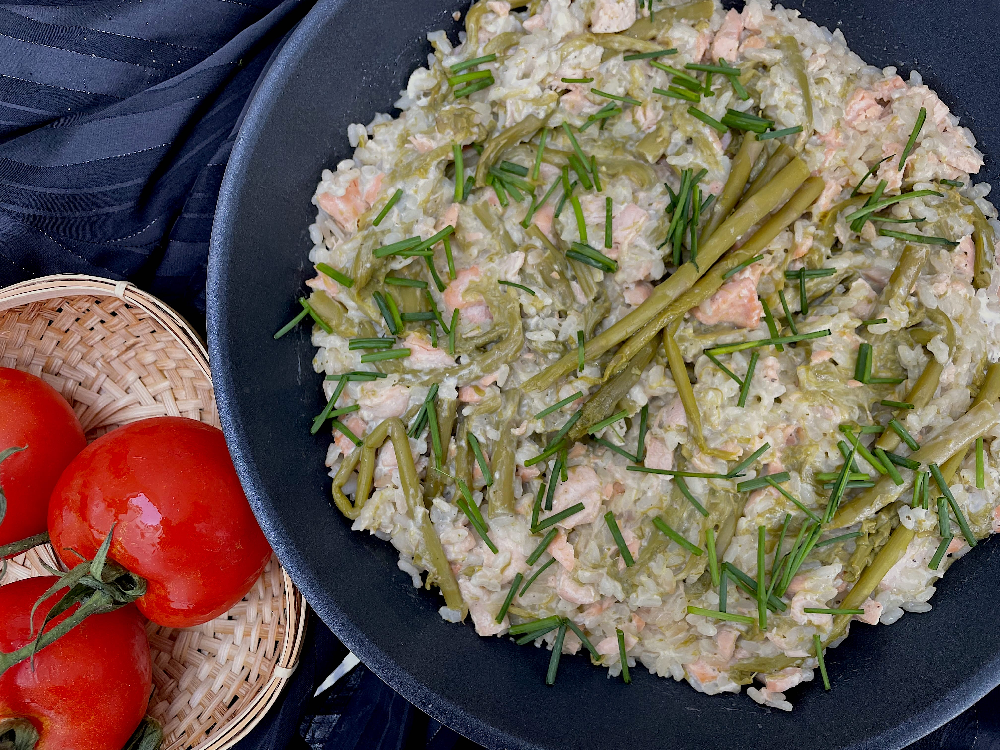 Le risotto est présenté dans un saladier bleu. Le saumon est recouvert par le riz. Les asperges et la ciboulette émincée sont sur le dessus du plat.
