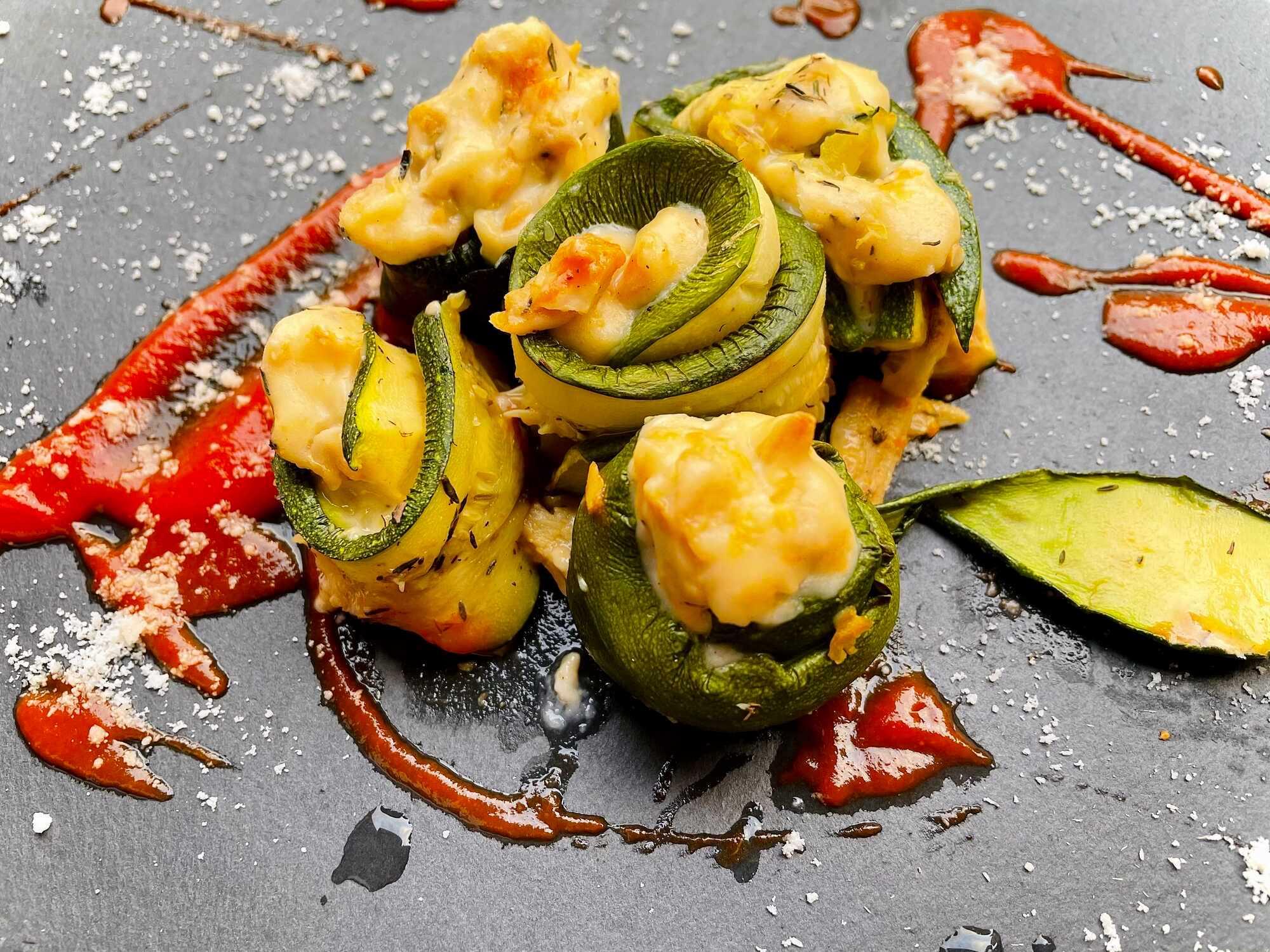 Les roulés de courgettes sont disposés sur la plaque de cuisson de couleur grise. Une harmonie de couleurs pour ce plat goûteux
