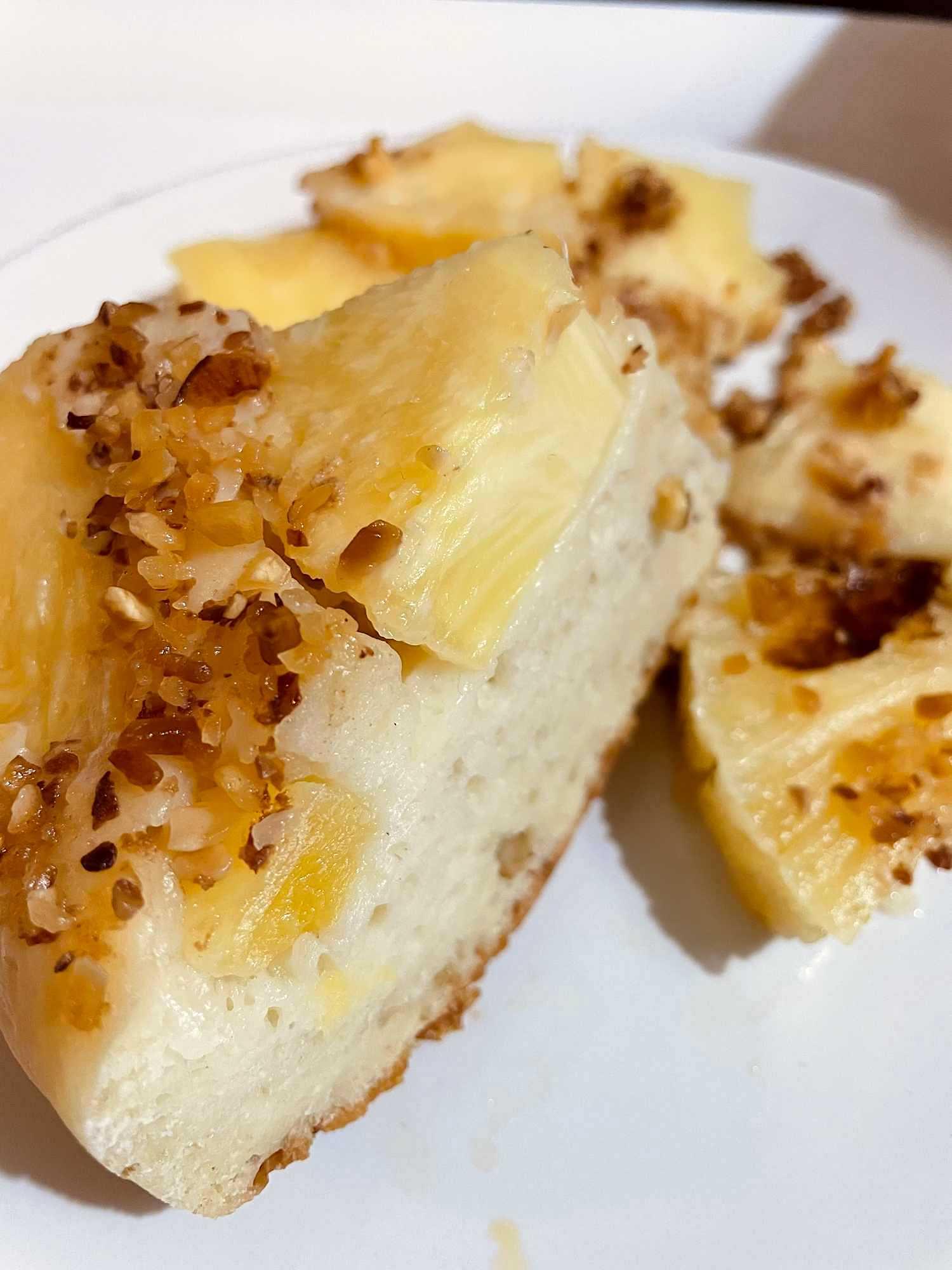 Deux belles parts de ce gâteau au fromage blanc sont présentés sur une assiette blanche. Le pralin est parsemé sur le dessus.