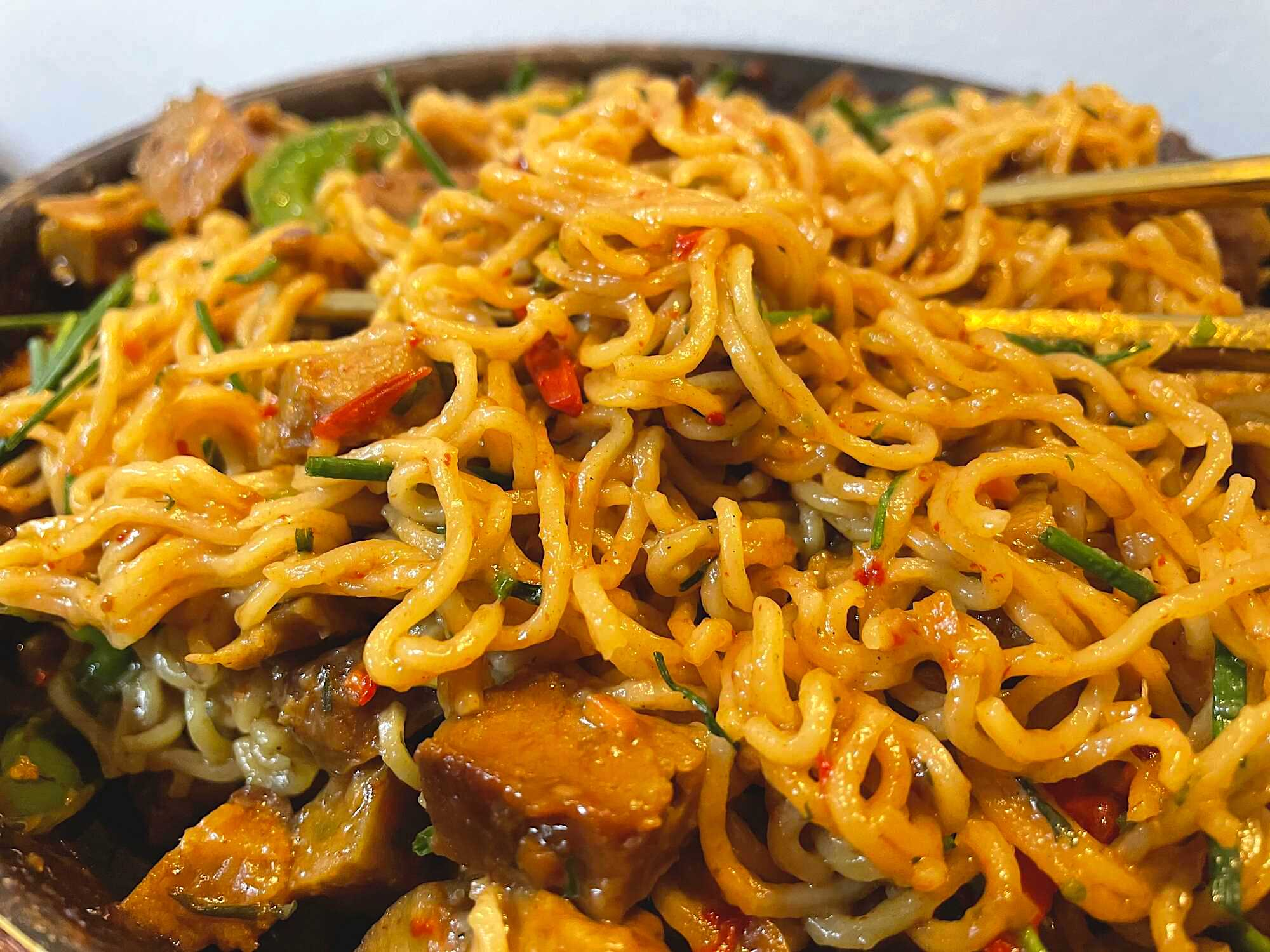 Les nouilles joliment colorées par la sauce soja, recouvrent les poivrons rouge et jaune : Effet visuel garanti avant la dégustation.