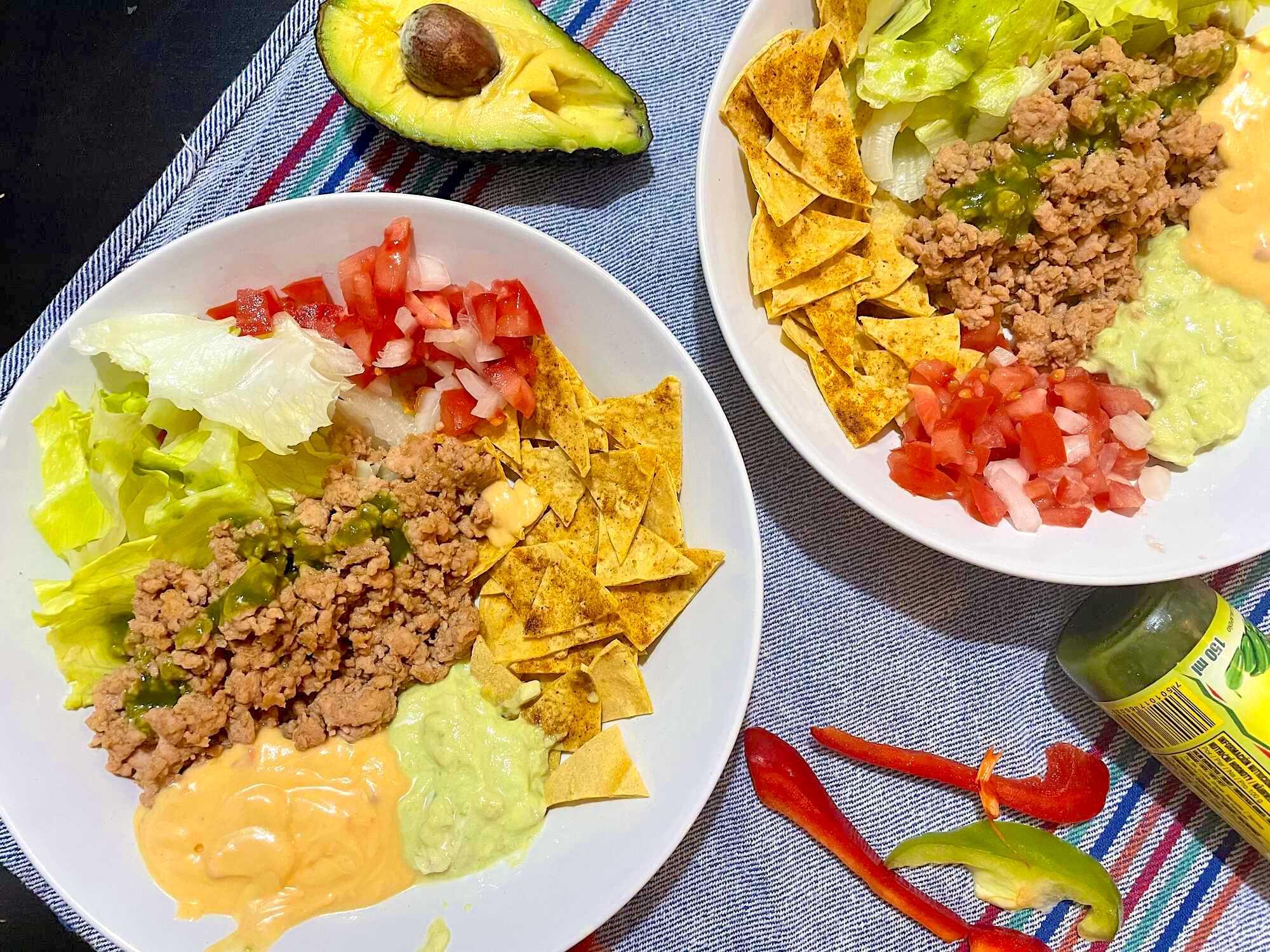 Sur une table sont disposées deux assiettes avec les nachos, les tomates, les oignons, la purée d'avocat et la viande de boeuf hachée.