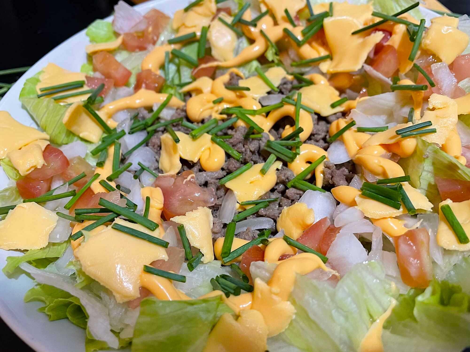 Tous les ingrédients de cette salade façon burger sont disposée sur un plat de couleur blanc. La ciboulette participe à l'effet visuel.