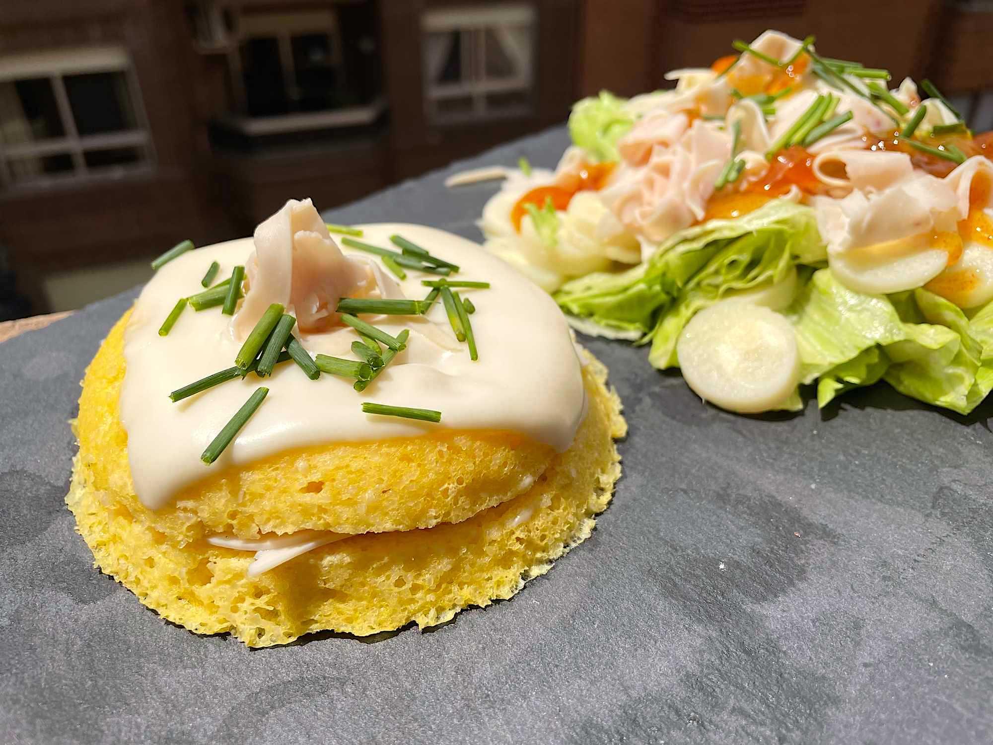 La semoule reproduit l'aspect du pain de mie qui compose un croque monsieur traditionnel. Une salade, laitue, tomates et oignons accompagne ce plat.