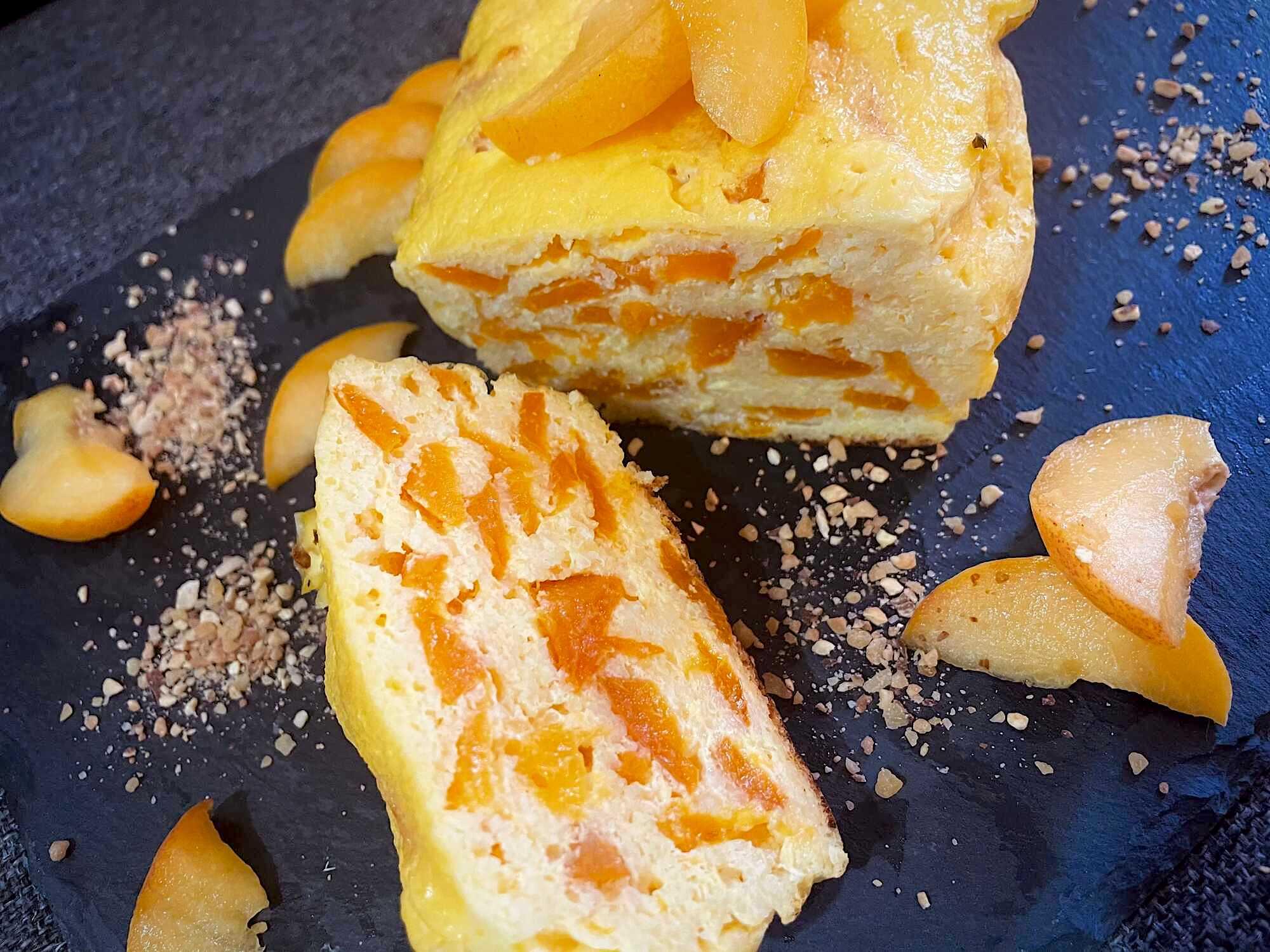 Deux belles parts du gâteau de semoule et abricots sont présentes sur un plat de couleur noir, elles montrent tout le moelleux de la recette.