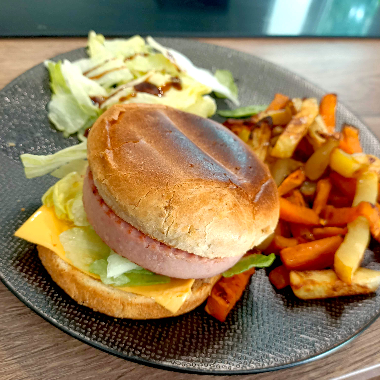 Sur une belle assiette en faïence de couleur noire , le burger de jambon est accompagné de frites et de quelques feuilles de salade.