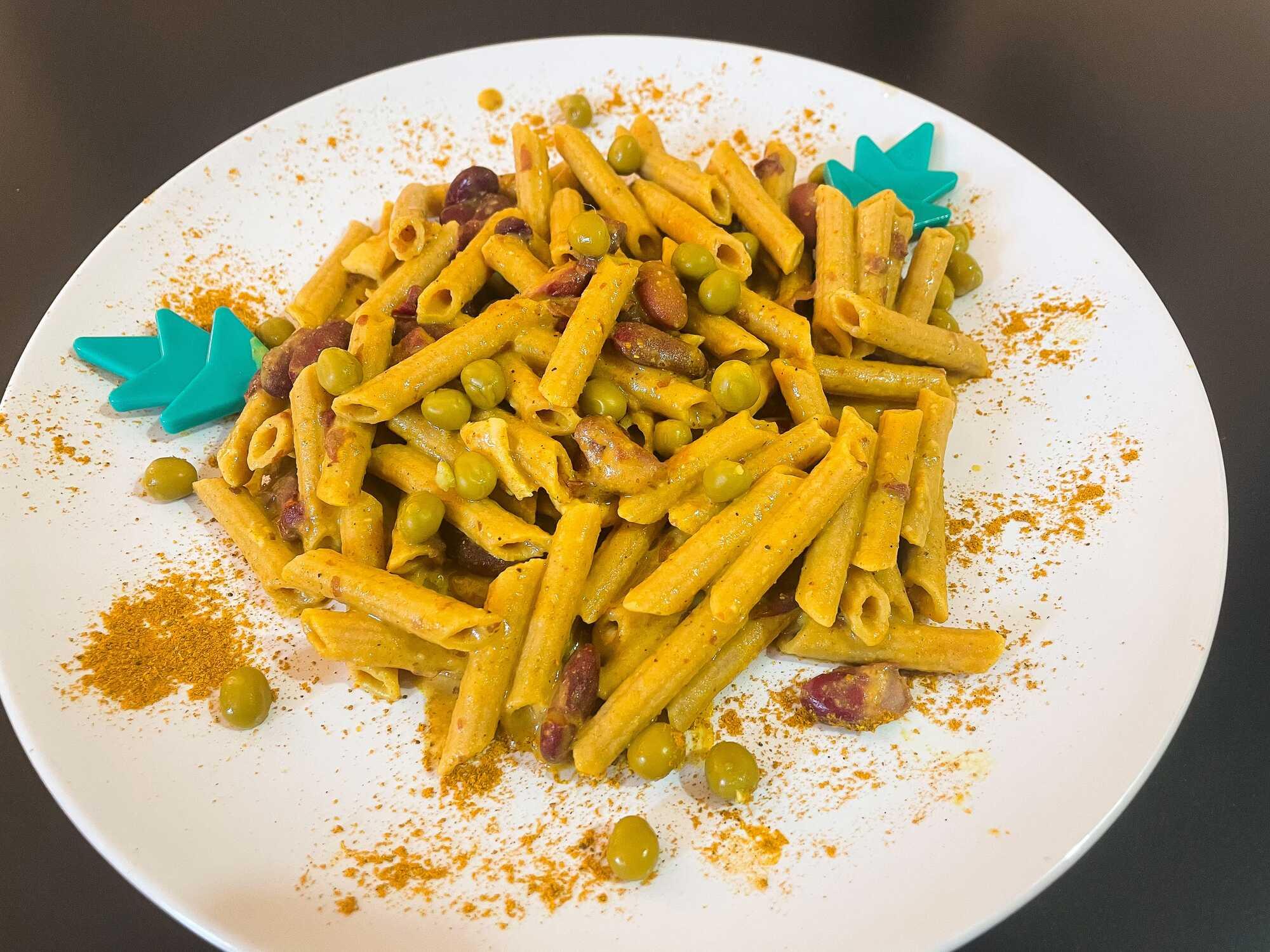 Le curry a teinté les pâtes crémeuses, elles recouvrent le poulet et le reste des ingrédients.