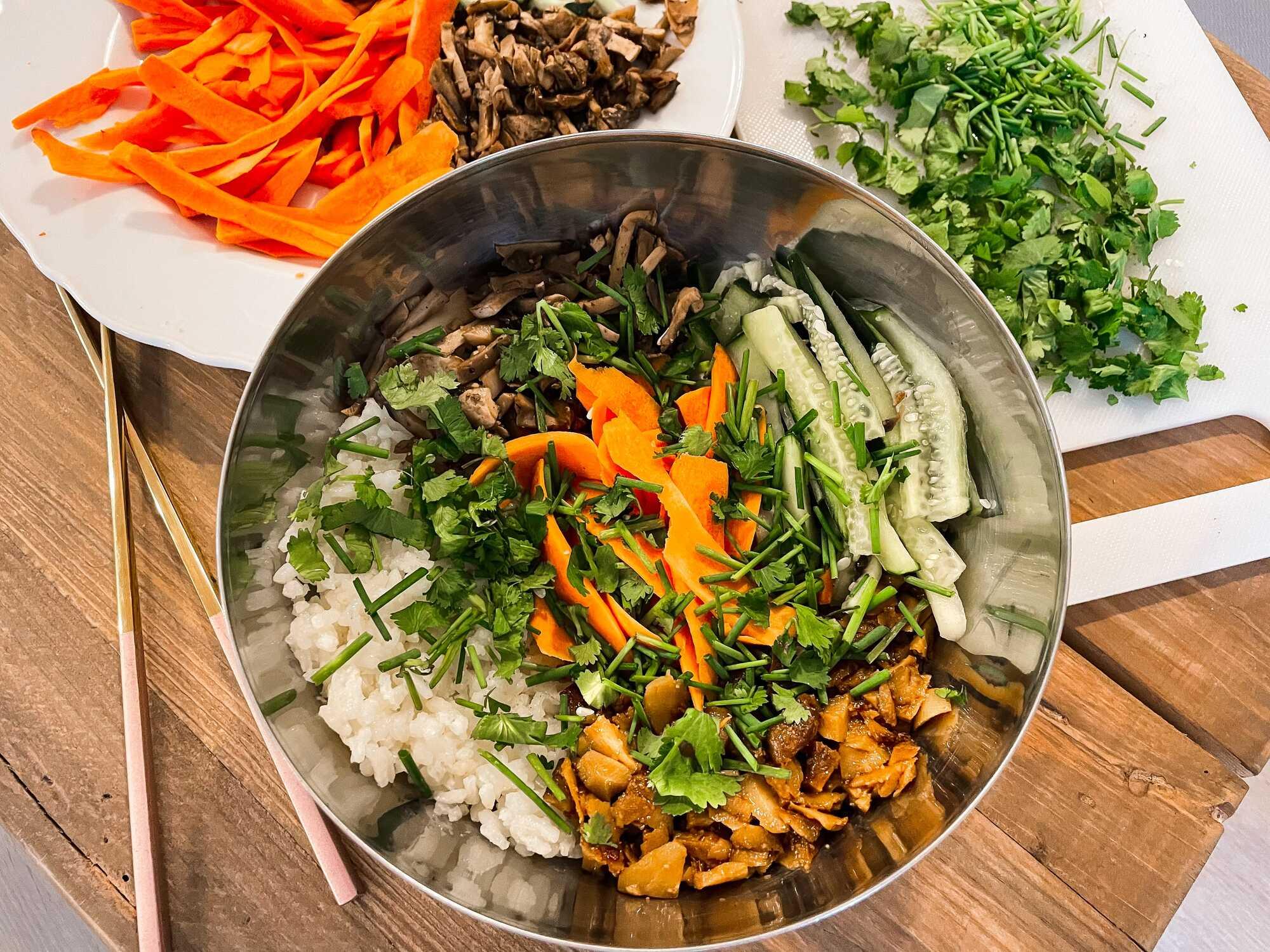Dans un large bol, le riz est disposé sur le fond, il est recouvert par les légumes. Persil et ciboulette ciselée accompagnent cette recette.