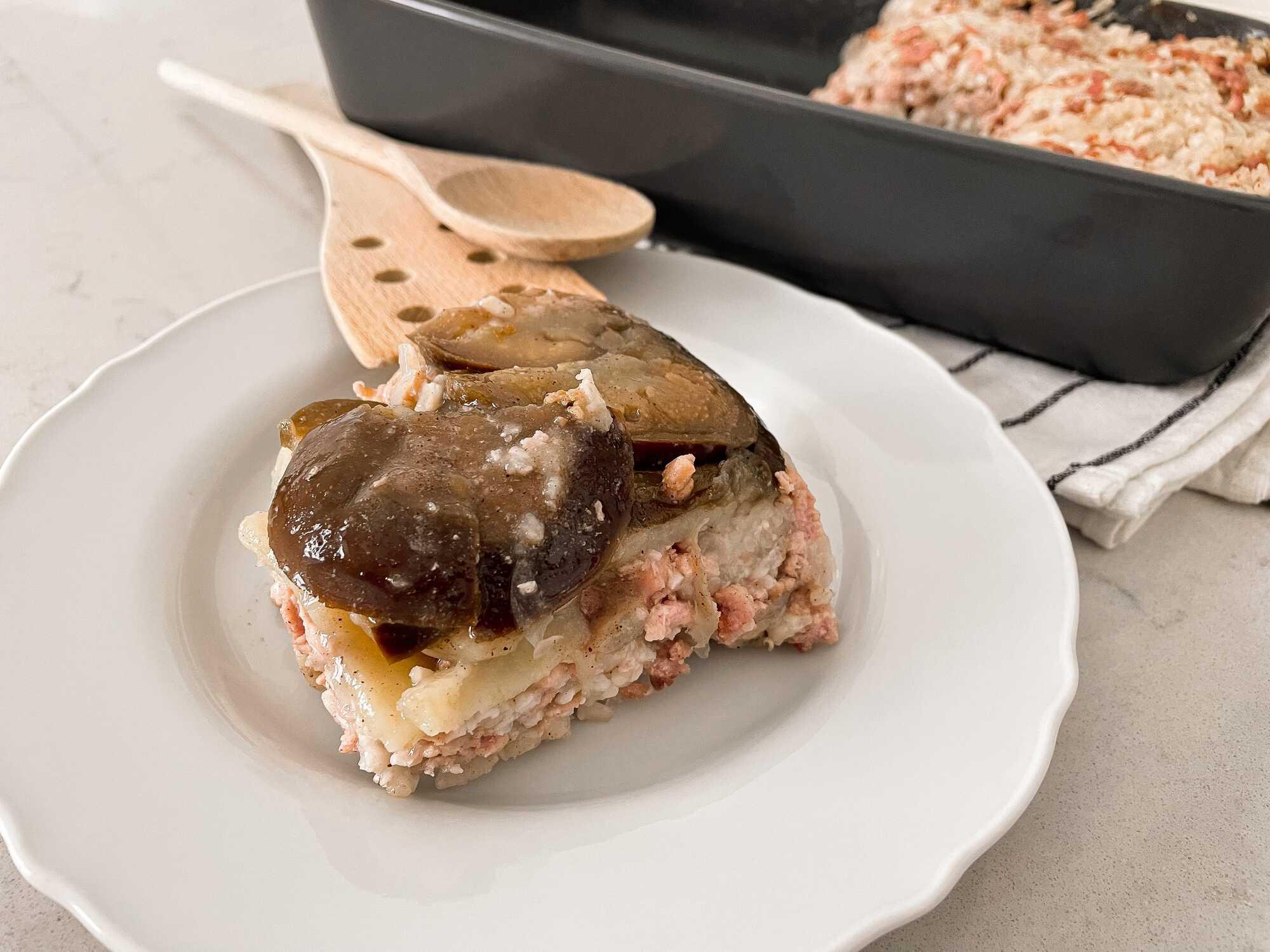 Sur une assiette de couleur blanche est présenté une grosse part de Maklouba. Les aubergines en couches épaisses recouvrent la préparation.