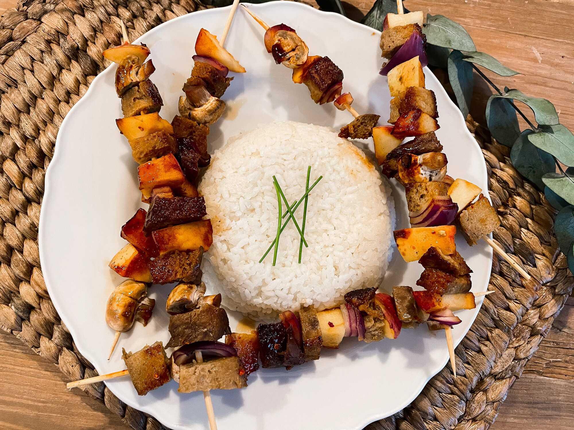 Au milieu d'une assiette de couleur blanche se trouve du riz blanc, entouré de cinq brochettes de seitan avec de la pomme et des champignons..