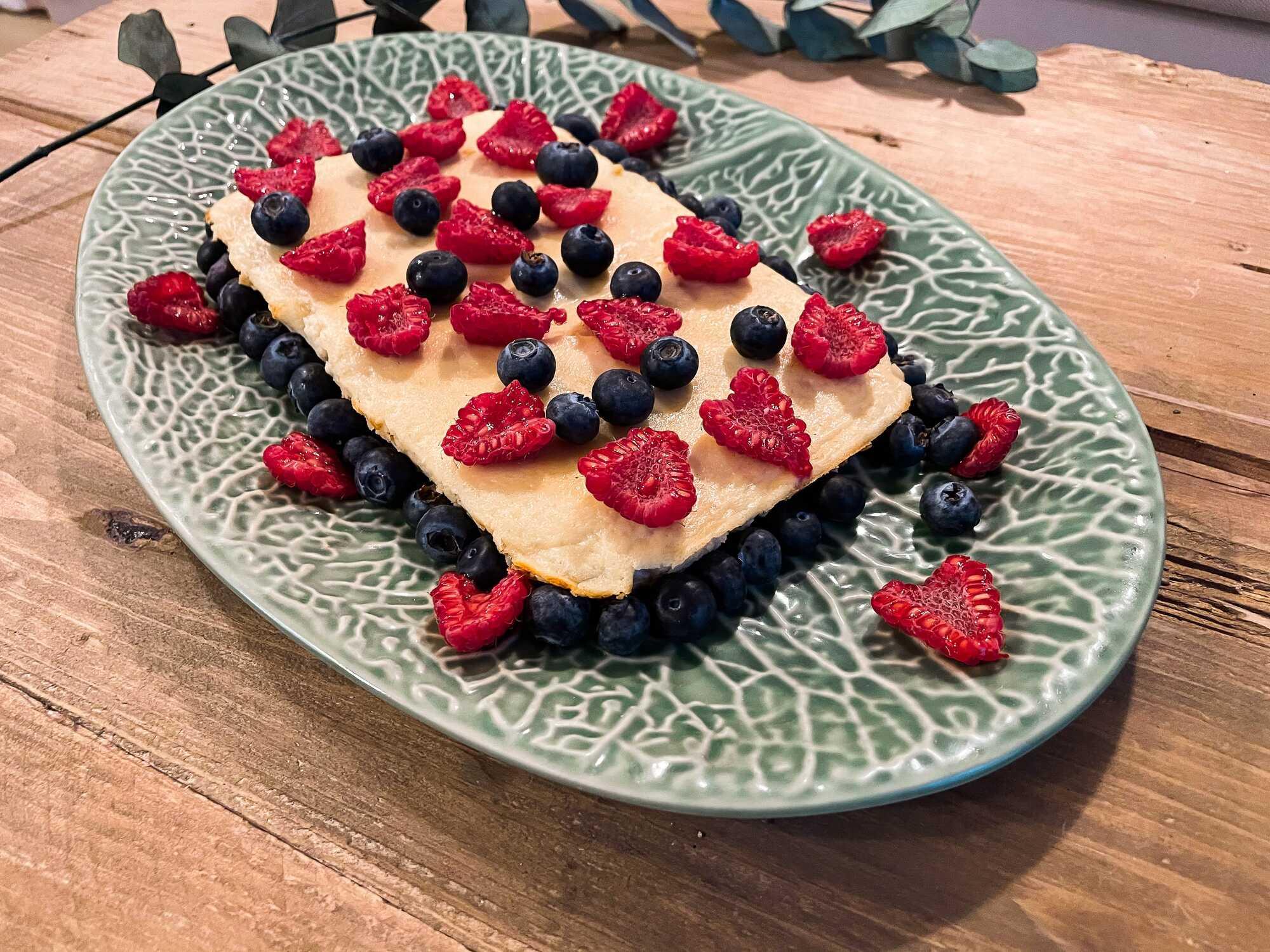 Disposé sur un plat ovale de couleur bleu et blanc, le flanc à la banane est accompagné de demis groseilles et de myrtilles.