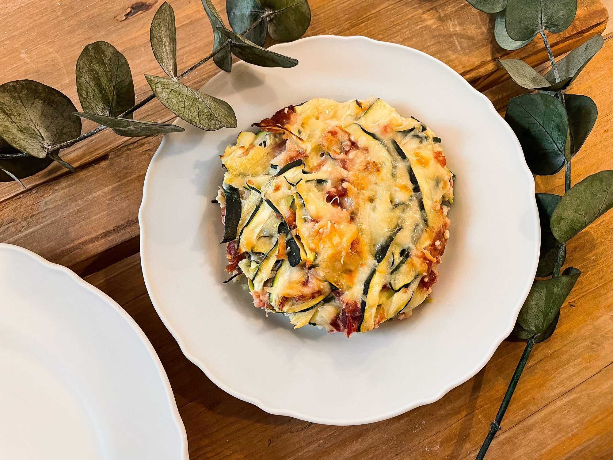 Présenté dans une assiette creuse de couleur blanche, disposée sur une table en bois clair, ce gratin semble très appétissant.