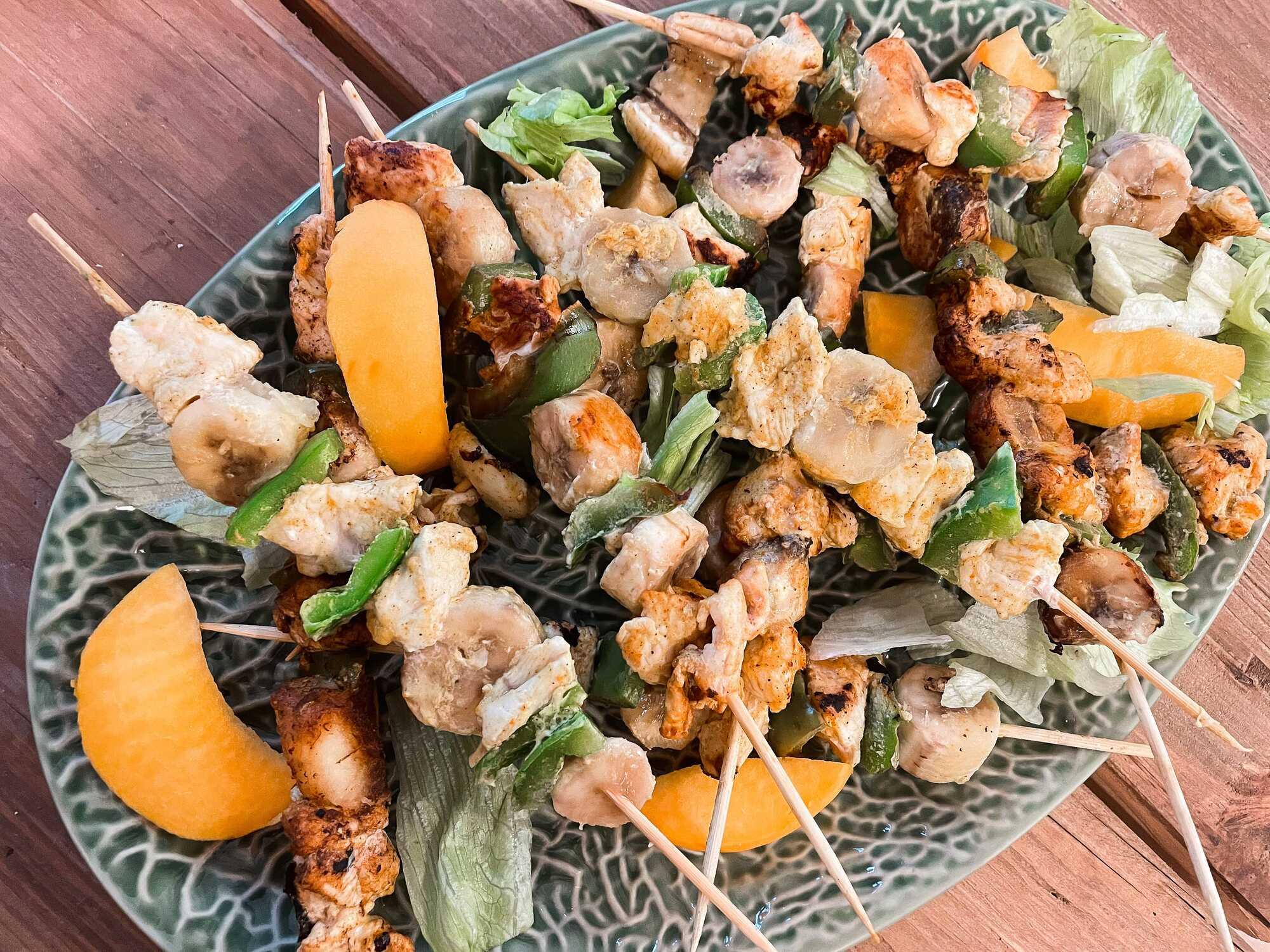 Sur un plat ovale sont disposées les brochettes. Quelques tranches de mangue décorent la recette. Effet visuel garanti !