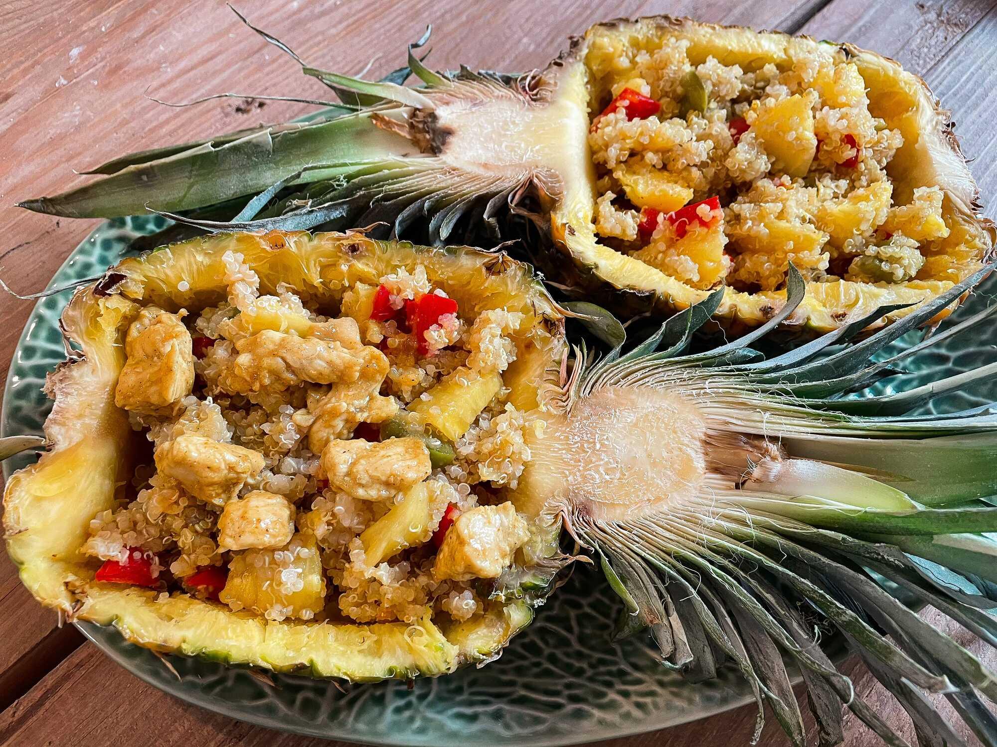 Sur une assiettes se trouve un ananas ouvert en deux dans le sens de la hauteur vidé de sa chair. L'ananas sert de réceptacle à la recette.