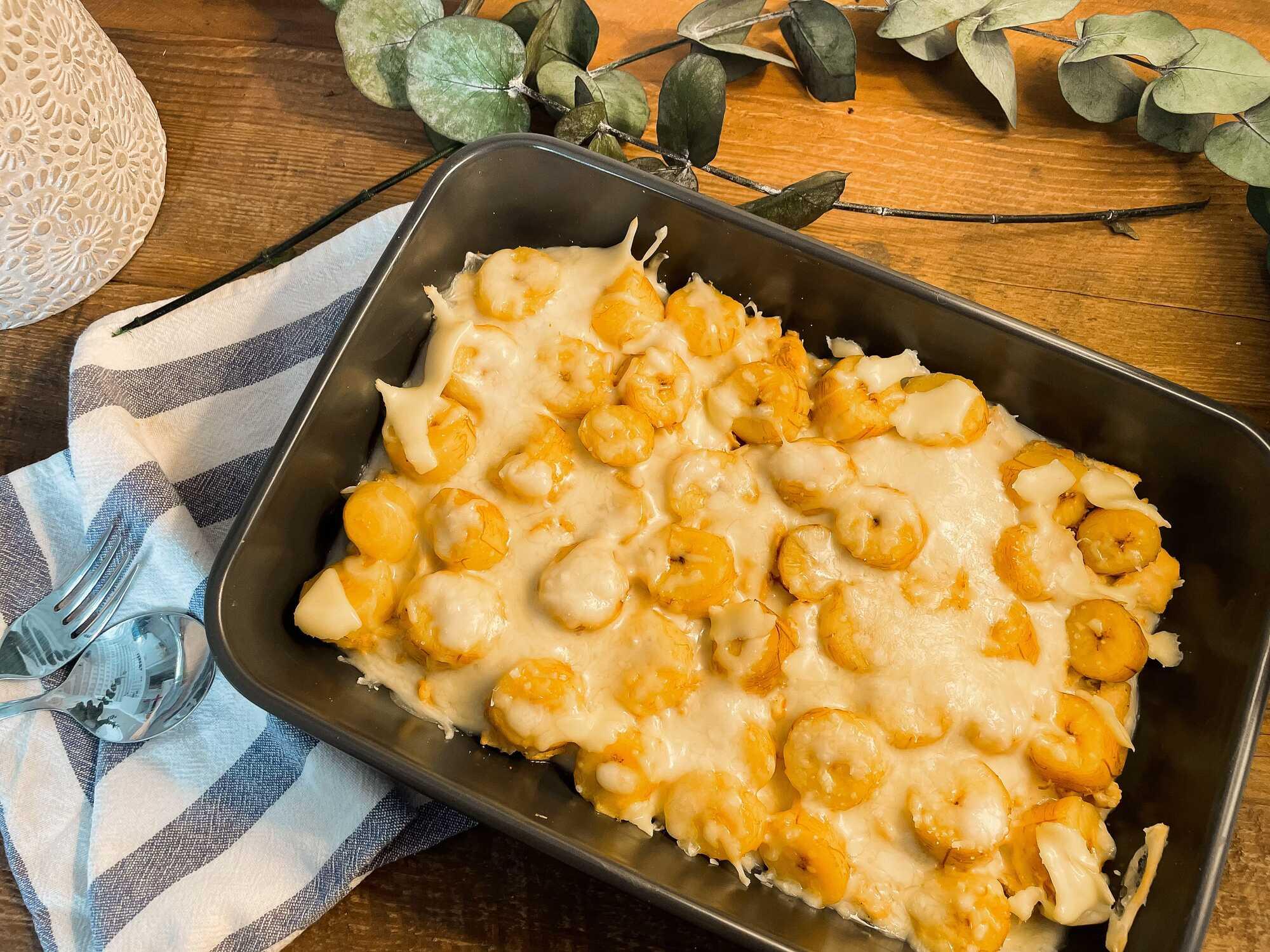 Présenté dans un plat à gratin. Sur son lit de filets de poulet, les bananes coupées en rondelles sont mélangées à la sauce Béchamel.