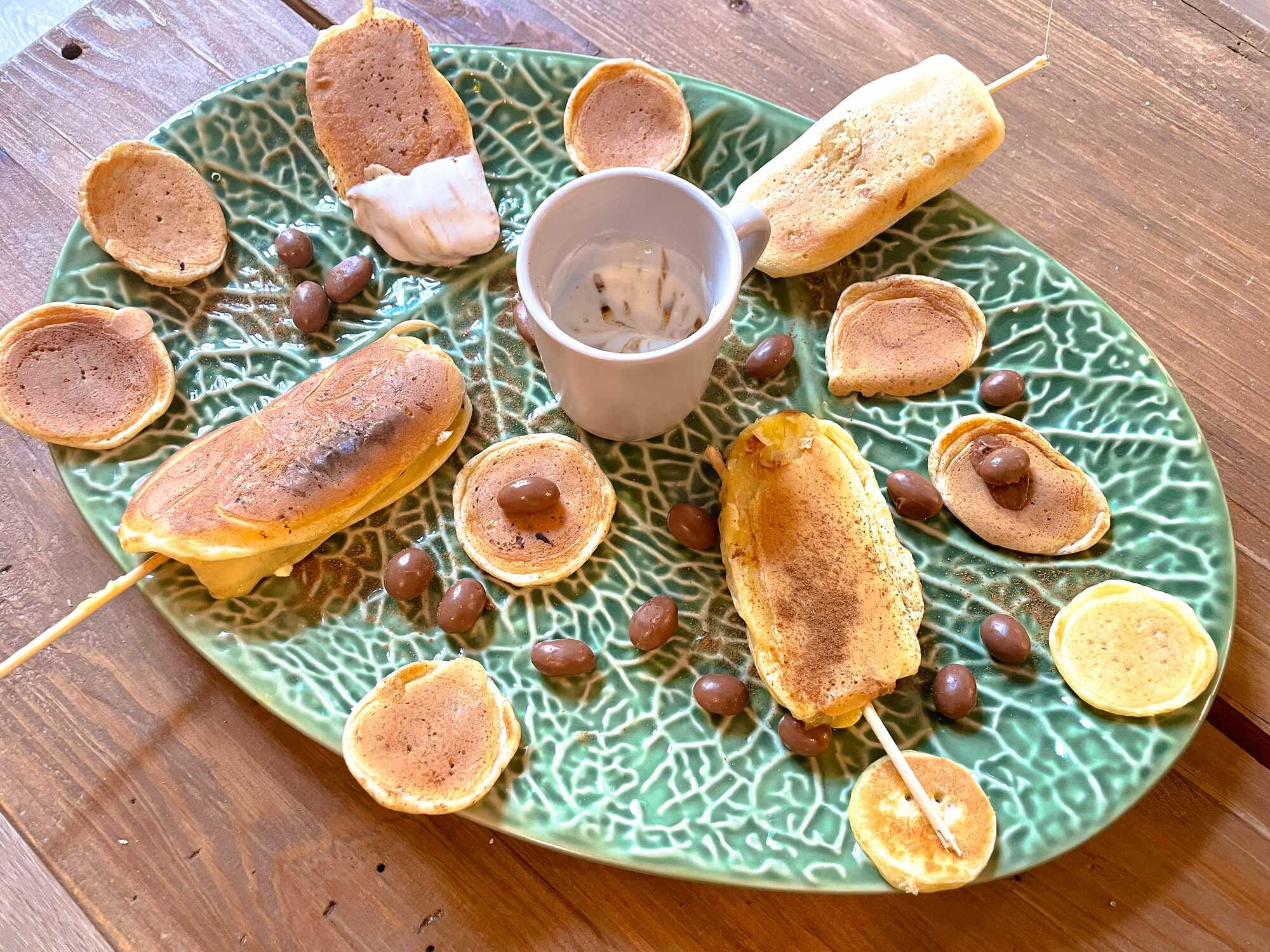 Les sucettes de pancake/banane sont accompagnées de pépites de chocolat, elles sont déposées sur un joli plat ovale de couleur vert.