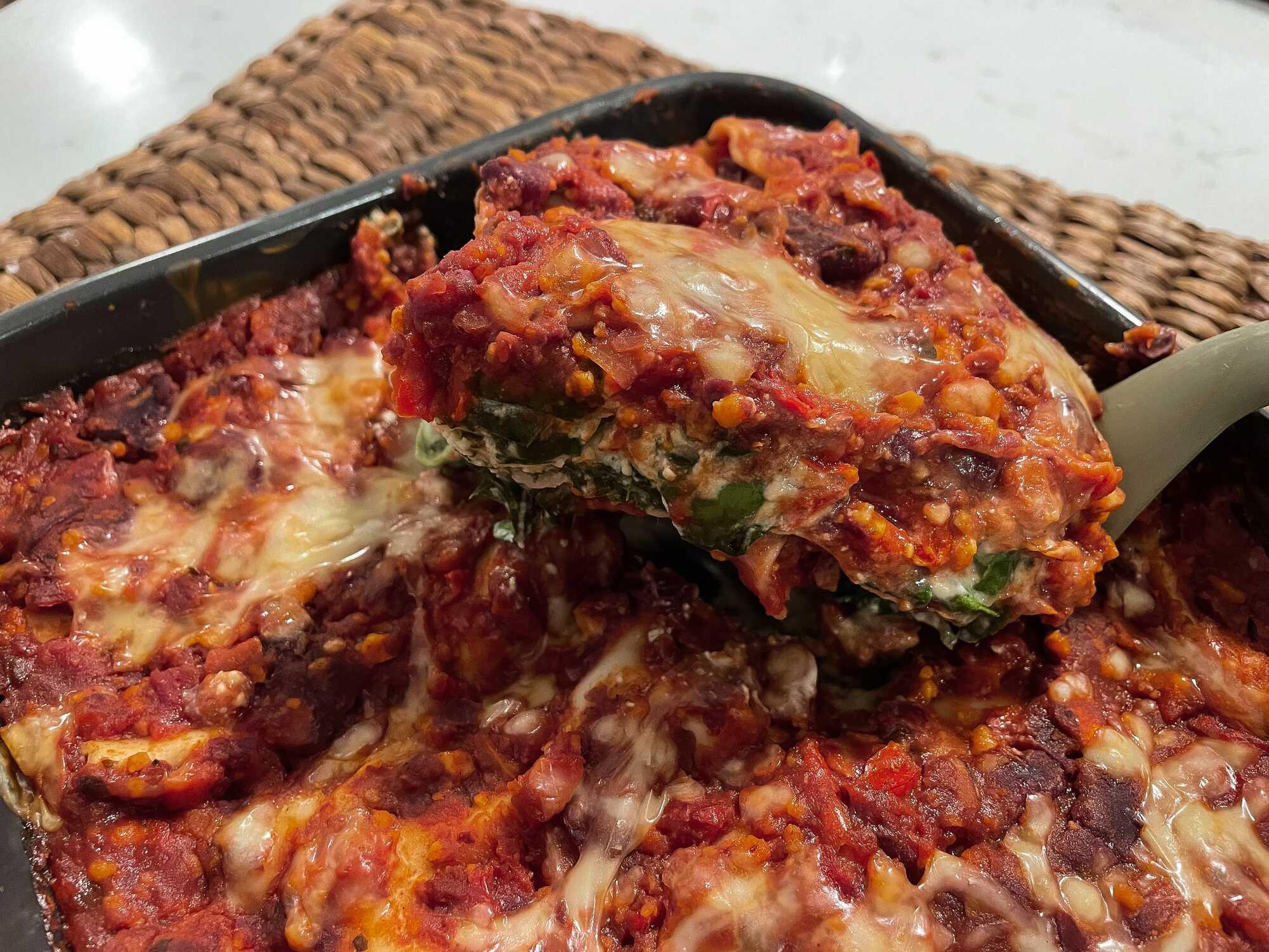 Les lasagnes végétariennes goûteuses et généreuses sont présentées dans un plat à gratin de couleur noir.
