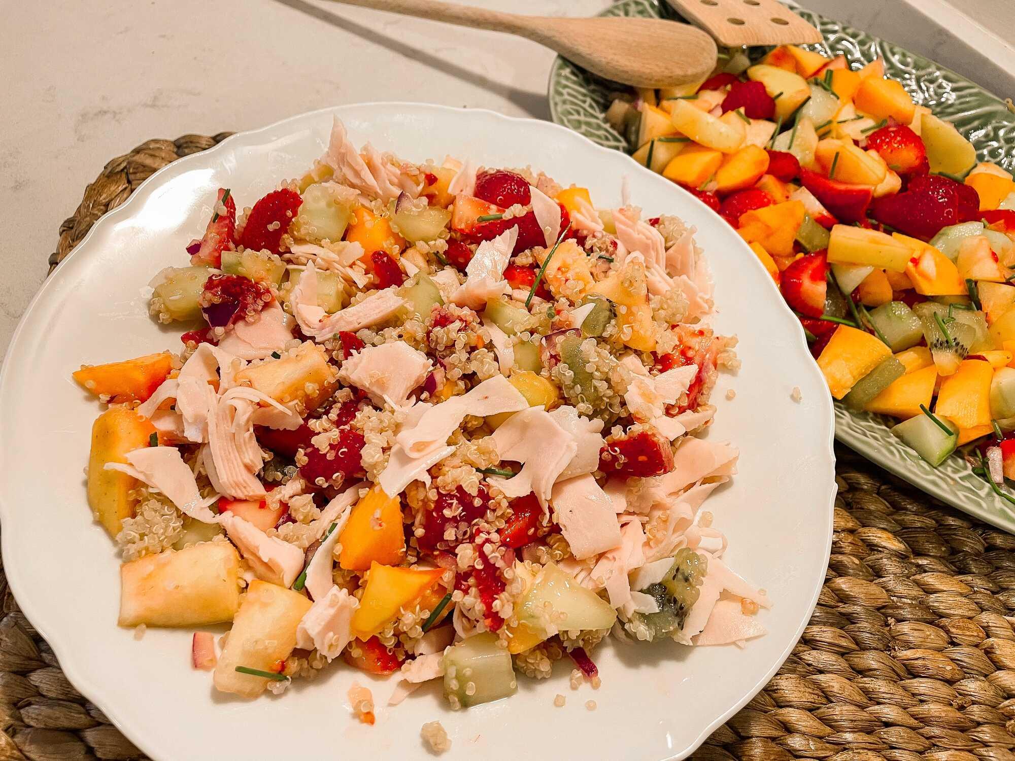 La salade de quinoa avec les fruits et le poulet sont disposés sur une assiette plate de couleur blanche.