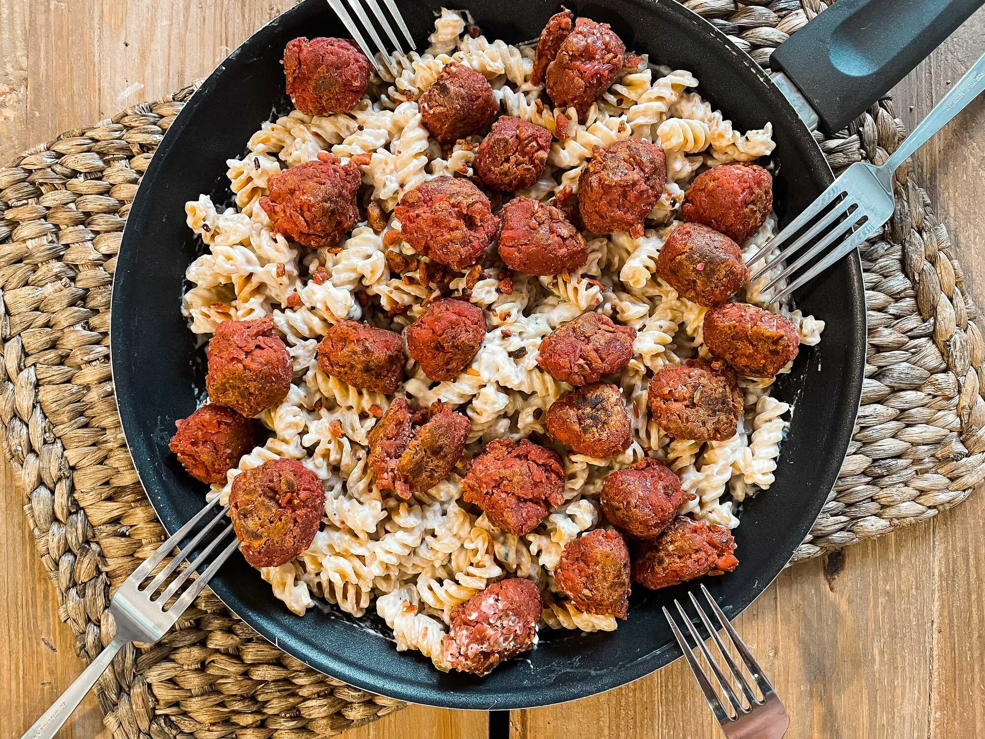 Dans une poêle se trouvent les pâtes à la crème parsemées de boulettes végétariennes de couleur rouge qui ressemblent à des boulettes de viande.