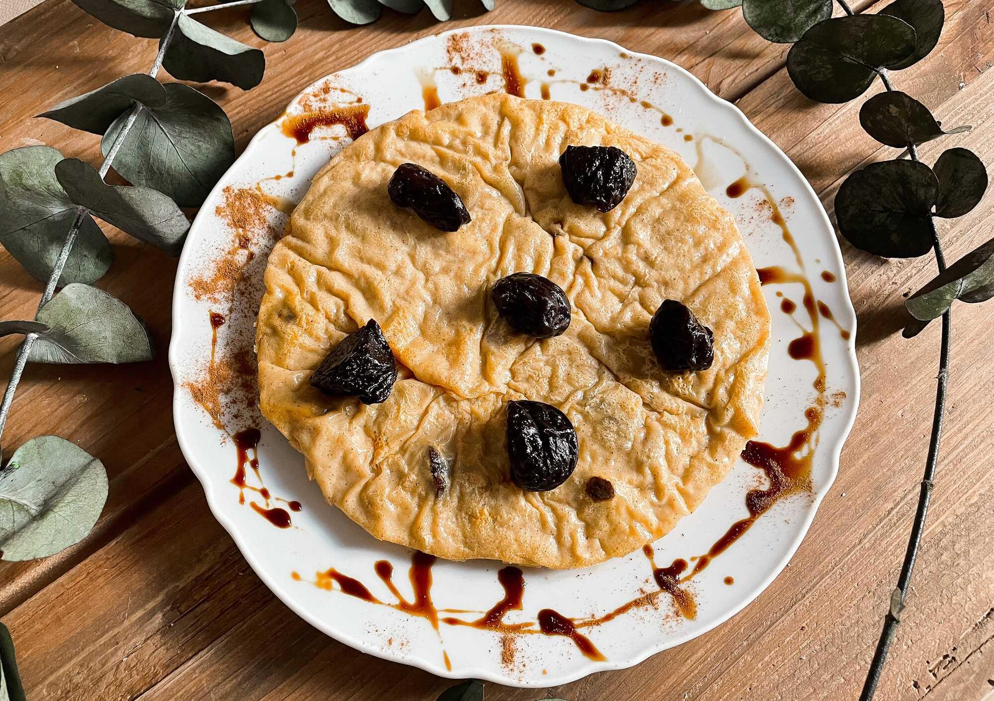 Sur une table en bois se trouve une assiette de couleur blanche dans laquelle est disposé le far breton aux pruneaux.