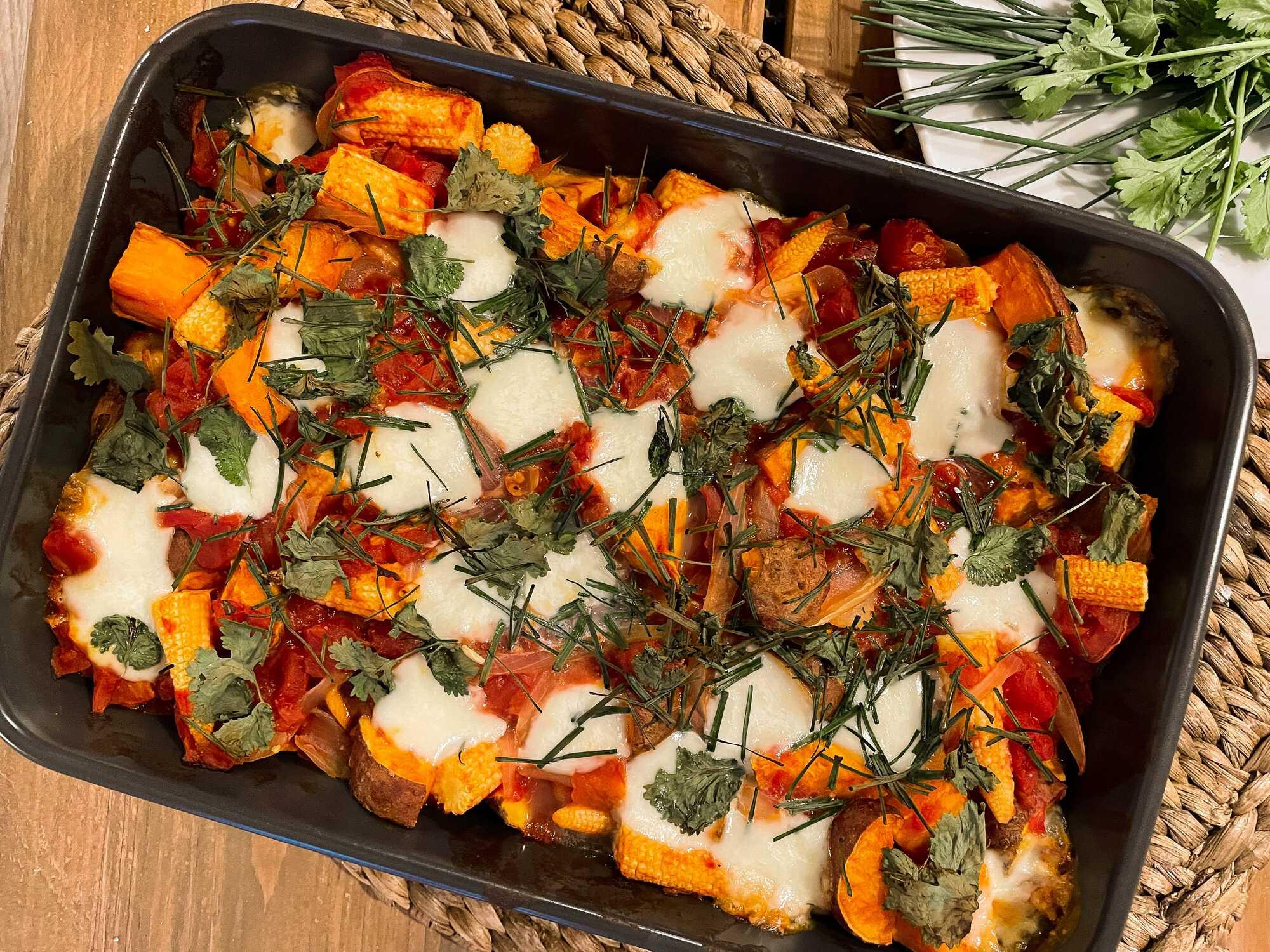 La recette de patates douces rôties aux boulettes de boeuf est exposée dans un plat à gratin avec quelques herbes aromatiques pour la décoration.