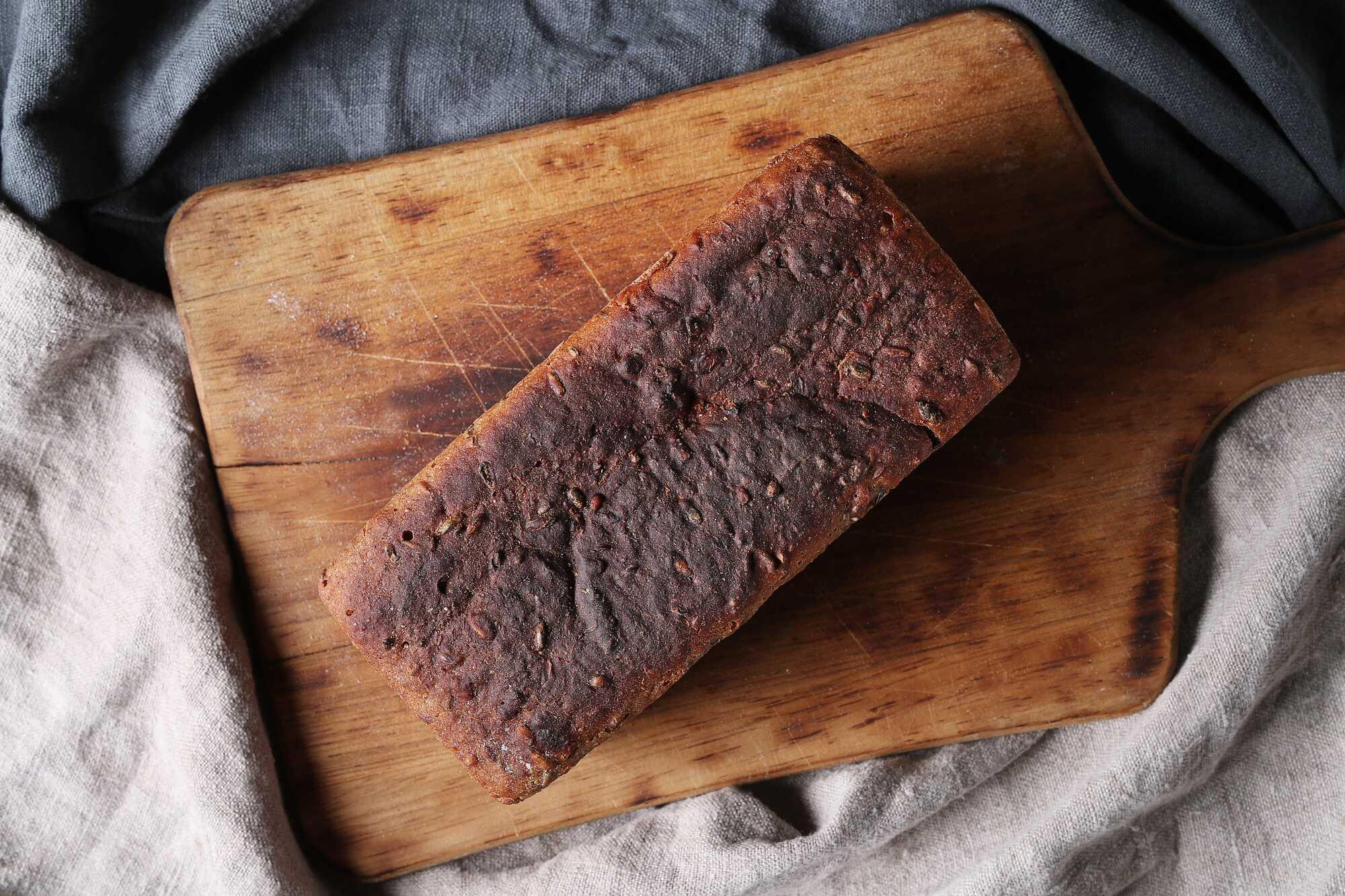 Pain au son d'avoine posé une planche à pain avec des torchons gris autour