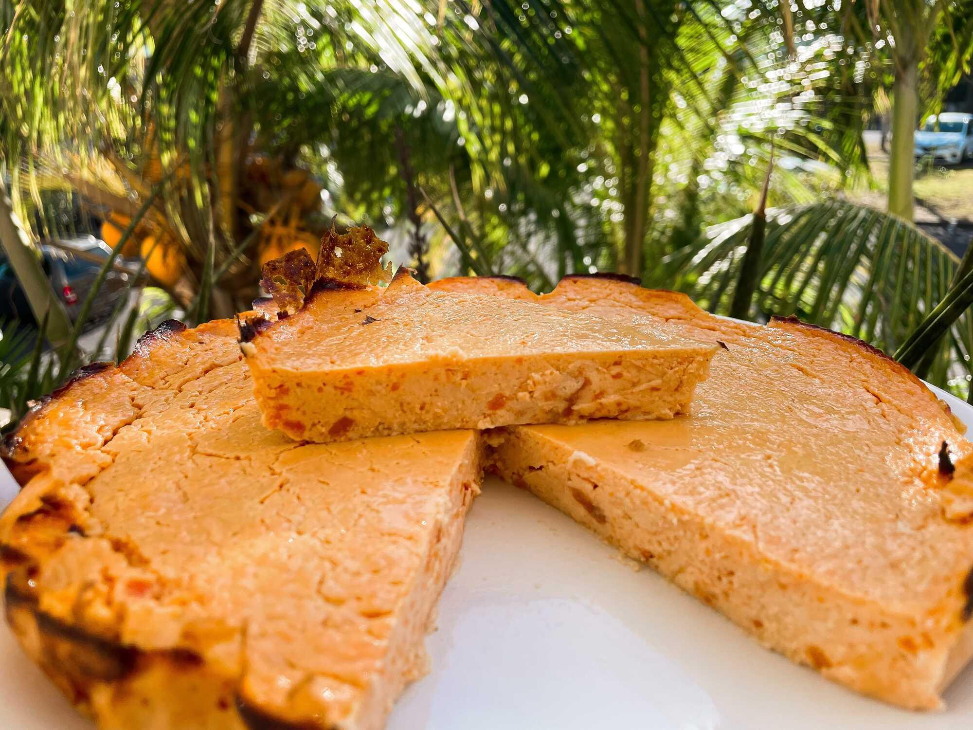 Gâteau de patate douce coupé et présenté sur une assiette blanche au milieu de feuilles.