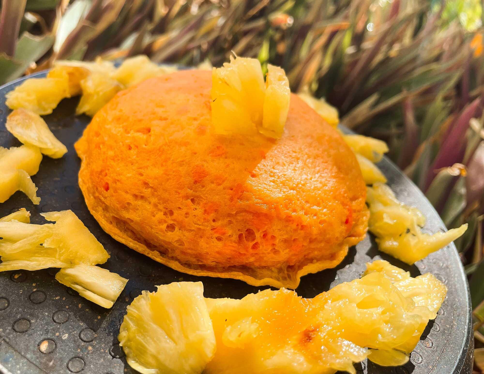Gâteau orange et rond présenté sur une assiette noire au-dessus de feuilles et décoré d'ananas frais coupé grossièrement.